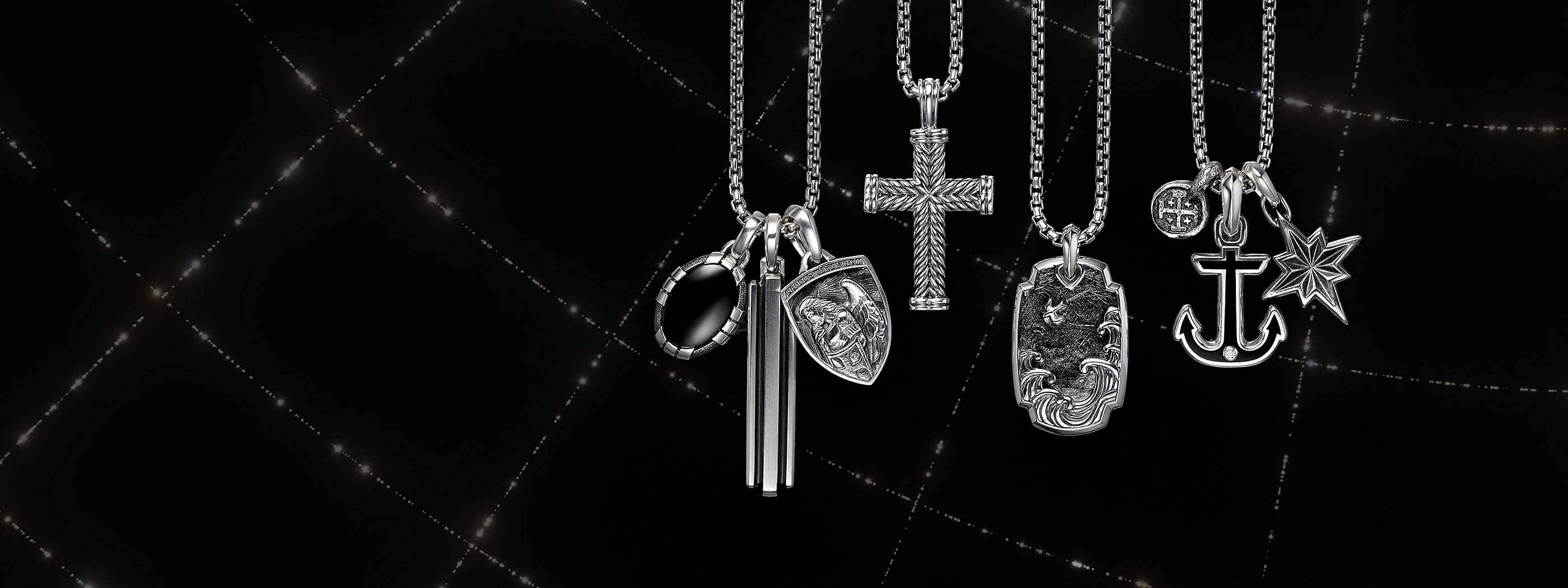 A color photograph shows four David Yurman men's box-chain necklaces in sterling silver arranged in a row in front of a black background with white latitude and longitude lines. Each necklace is strung with one or three David Yurman men's amulets crafted from sterling silver. From left is a Southwest amulet with black onyx, a Deco amulet, a Saint Michael shield-shaped amulet, a Chevron cross, a Waves tag with forged carbon, a Shipwreck coin amulet, a Maritime anchor with black onyx and a single diamond and a Maritime North Star amulet.