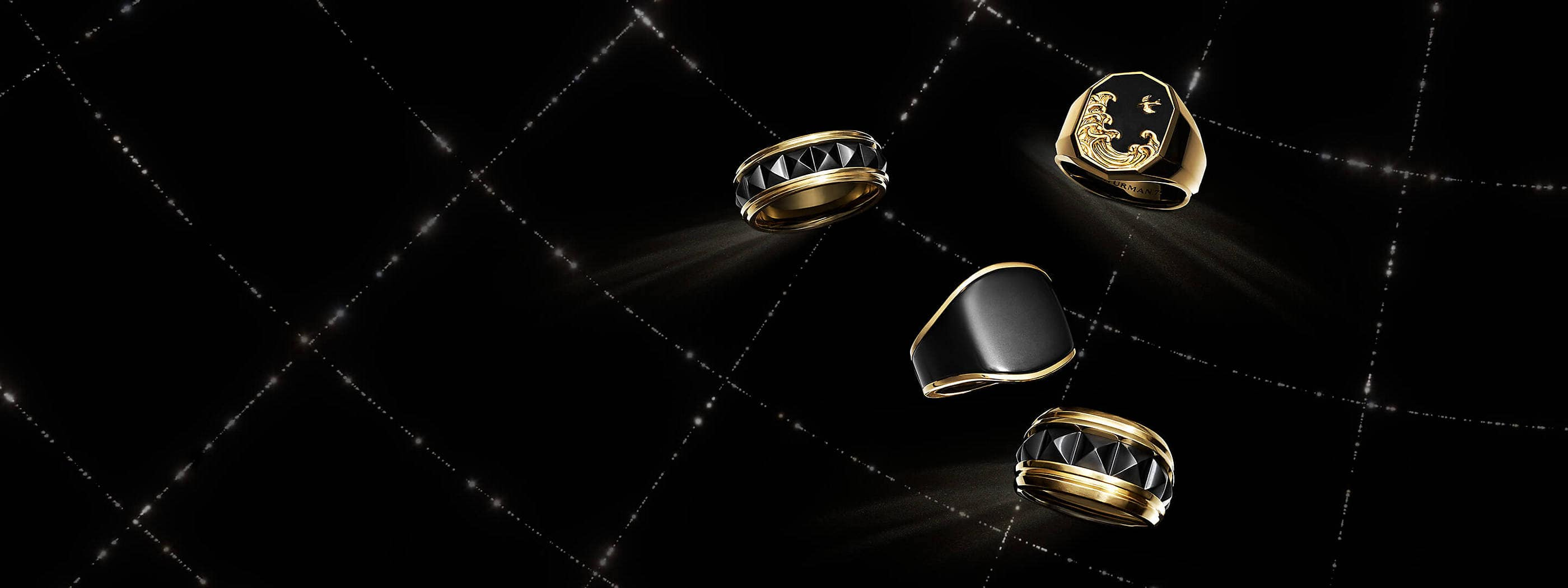 A color photo shows four David Yurman men's rings floating in a black background with white latitude and longitude lines. The jewelry is crafted from 18K yellow gold with or without forged carbon or black titanium.