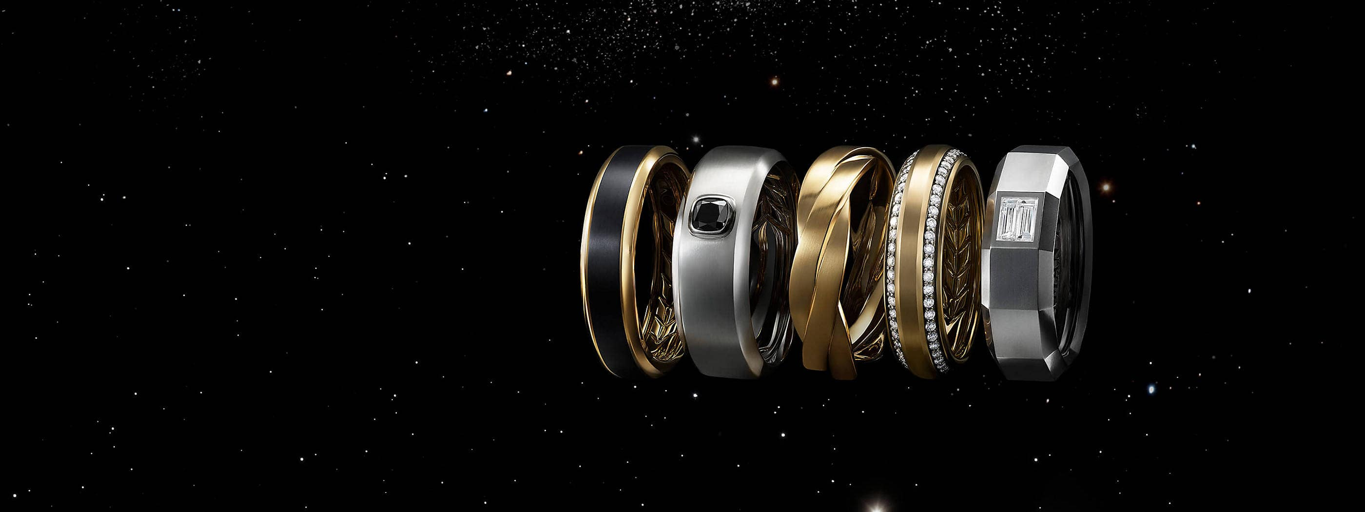 A color photo shows a horizontal stack of five David Yurman men's bands floating in front of a starry night sky. Three of the men's rings are crafted from 18K yellow gold with or without pavé white diamonds or black titanium. Two of the rings are crafted from 18K white gold with or without black or white diamonds