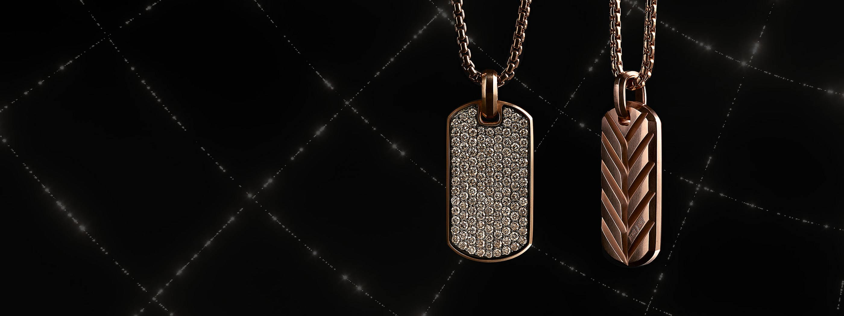 A color photograph shows two David Yurman men's tags and box-chain necklaces hanging in front of a black background with white latitude and longitude lines. The jewelry is crafted from 18K rose gold with pavé cognac diamonds.