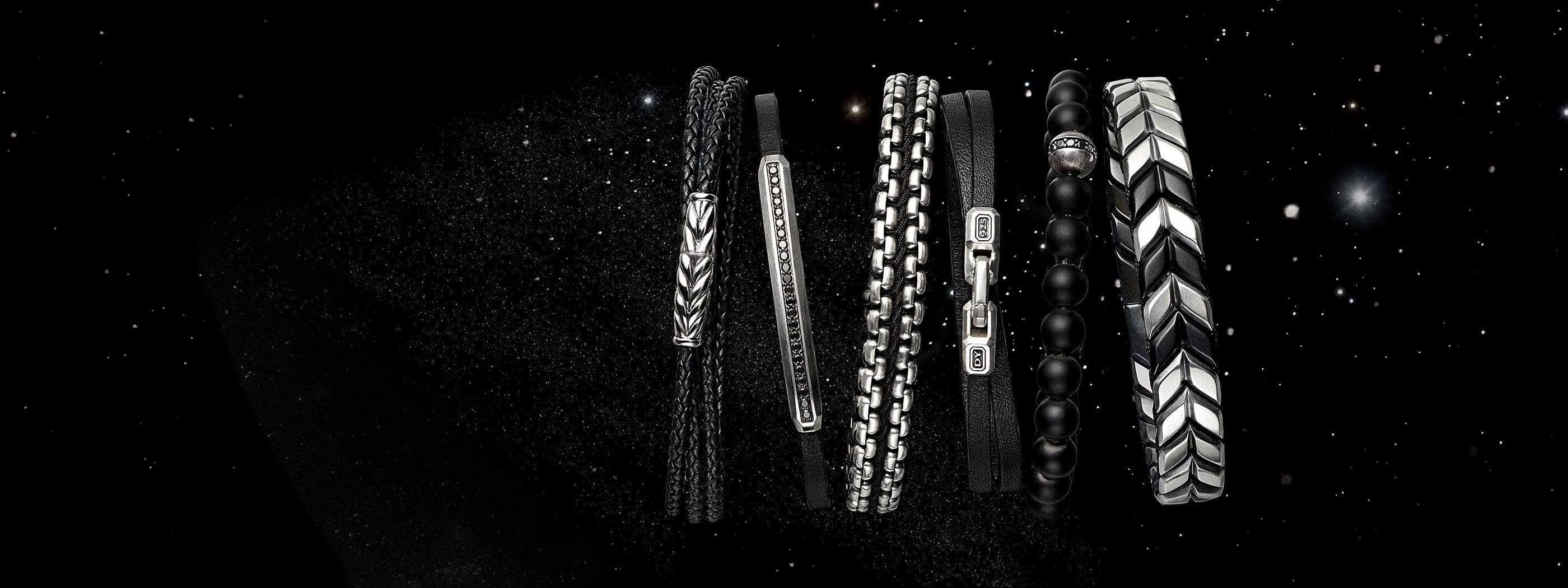A color photograph shows a horizontal row of six David Yurman men's bracelets standing in front of a starry night sky. The jewelry is crafted with sterling silver. From left is a Chevron bracelet in sterling silver with braided black leather, a Pavé bracelet in sterling silver with smooth black leather and pavé black diamonds, a Chain bracelet in sterling silver with woven black nylon, a Streamline bracelet with sterling silver and smooth black leather, a Spiritual Beads bracelet in black onyx with pavé black diamonds and a Chevron bracelet in sterling silver with black titanium.