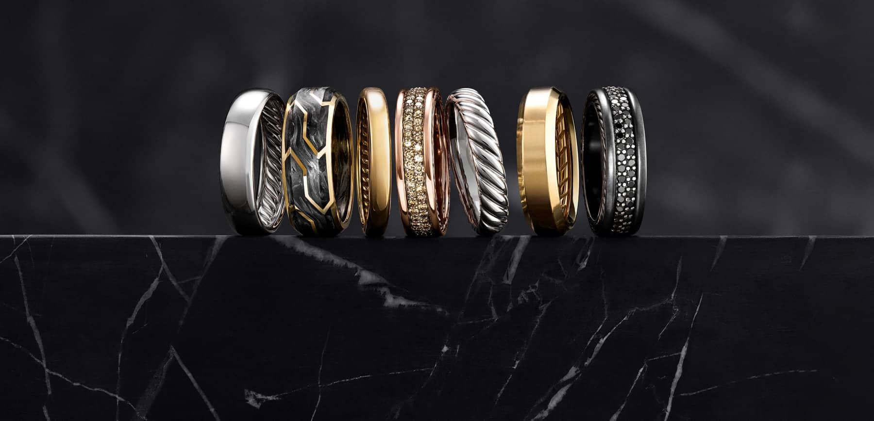 A color photograph shows a row of seven David Yurman men's wedding bands from the DY Classic, Forged Carbon, Streamline, Beveled and Cable collections atop a dark, marbled stone surface with a dark background. Each is crafted from 18K white, yellow or rose gold, 18K yellow gold and forged carbon, or black titanium with or without cognac or black diamonds.