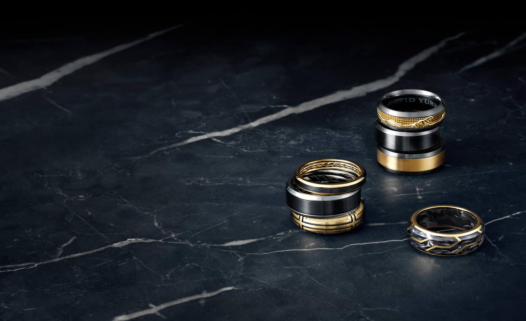 A color photograph shows three stacks of David Yurman's men's wedding bands from the Waves, Beveled and Forged Carbon and Southwest collections atop a dark, marbled surface. Each is crafted from black titanium and 18K yellow gold, black titanium, 18K yellow gold and forged carbon, 18K yellow gold or grey and black titanium.