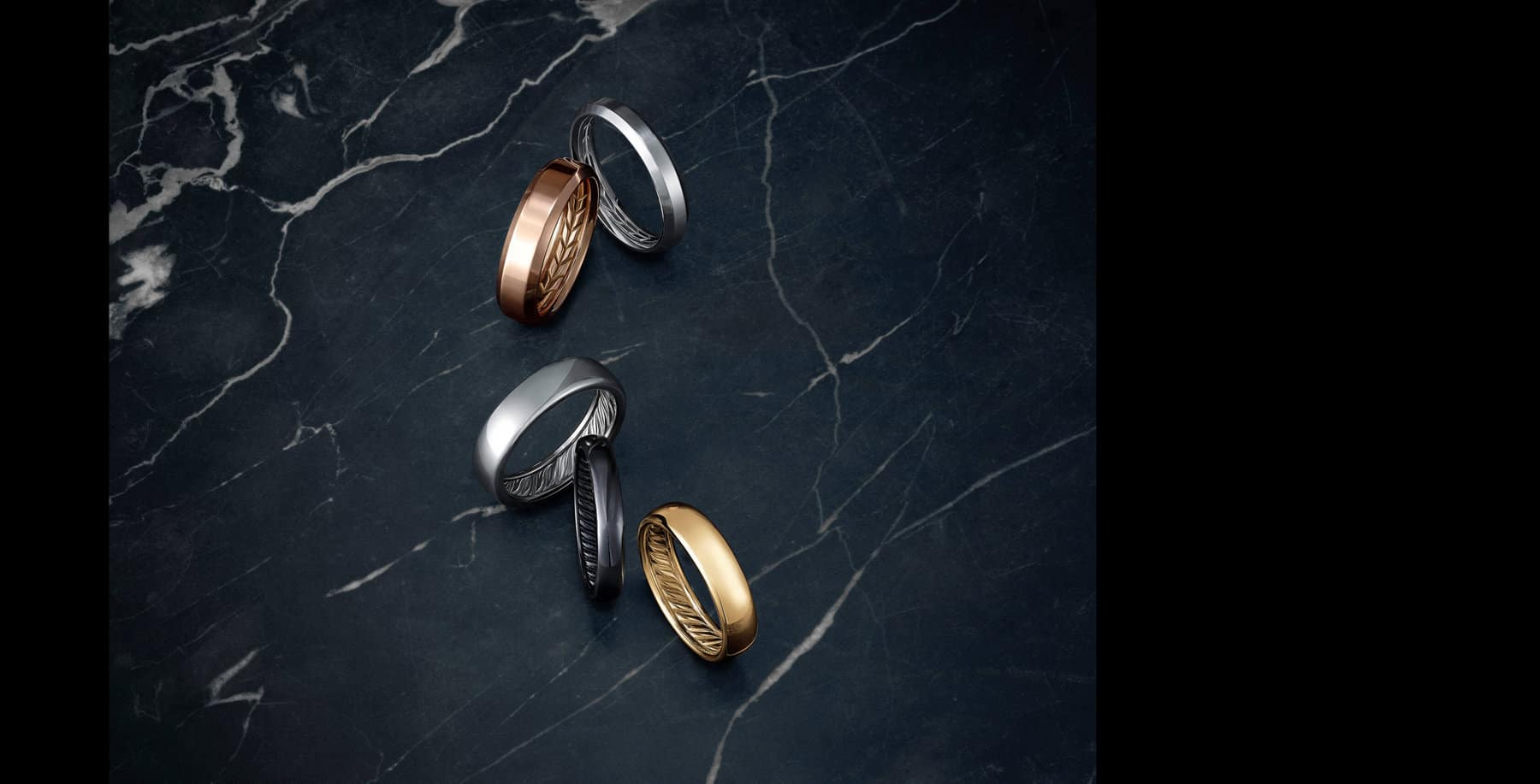 A color photograph shows five David Yurman Beveled and DY Classic men's wedding bands crafted from 18K white, yellow or rose gold or grey or black titanium. The bands sit atop a dark, marbled stone surface.