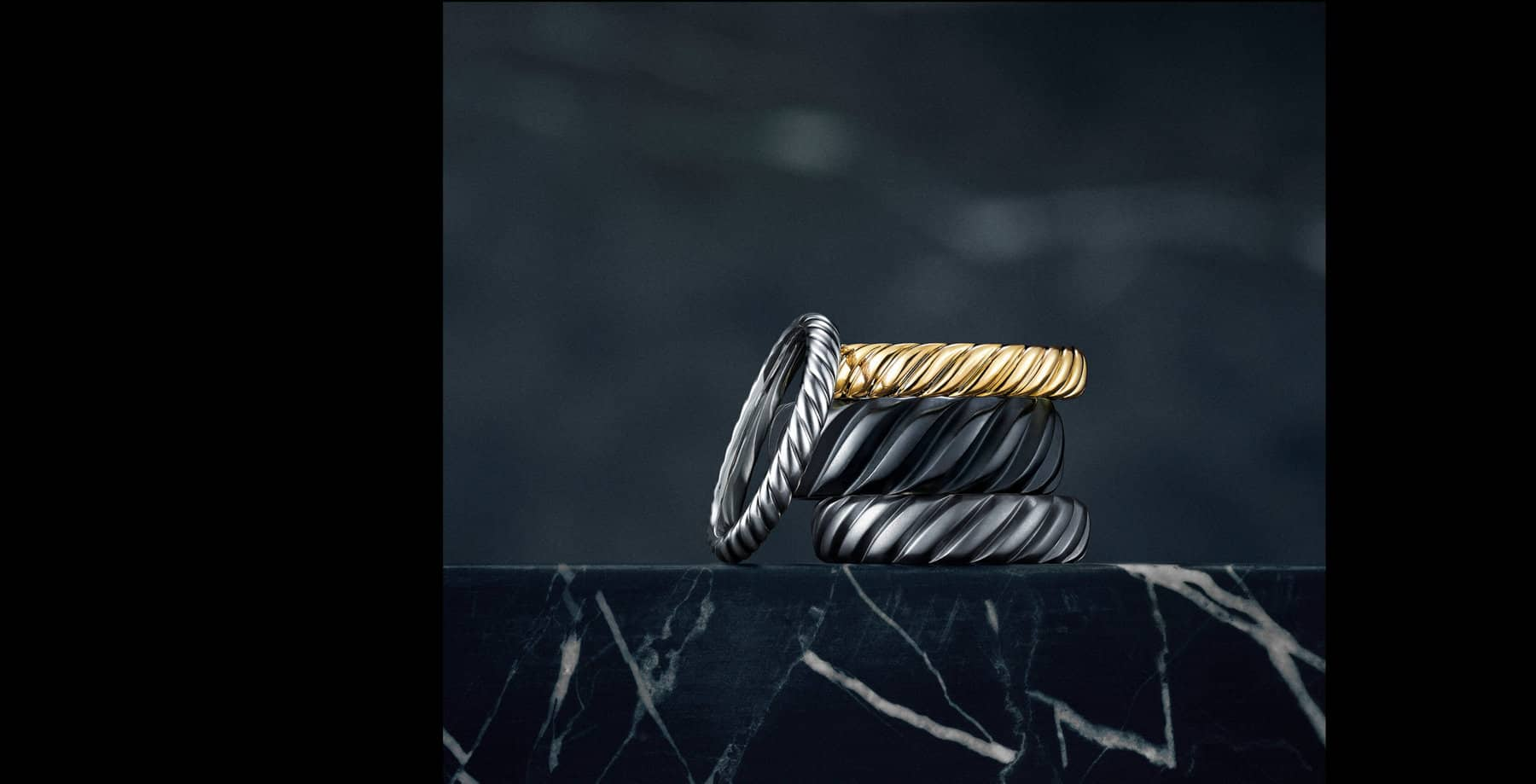 A color photograph shows an 18K white gold wedding band leaning against a stack of three wedding bands in 18K yellow gold and black or grey titanium. Each ring is from the Cable Collection. The rings sit atop a dark, marbled stone surface with a dark background.