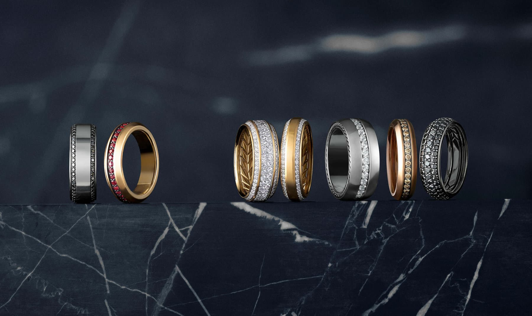 A color photograph shows a row of David Yurman men's wedding bands from the Beveled and Streamline collections atop a dark, marbled stone surface. The bands are crafted from 18K yellow, white or rose gold, grey titanium, or sterling silver and grey titanium with or without white, black or cognac diamonds or rubies.