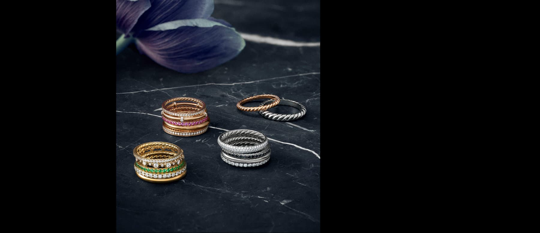 A color photograph shows four stacks of David Yurman women's wedding bands crafted from 18K rose gold, platinum or 18K yellow gold. The bands shown are from the DY Eden, DY Astor, DY Unity and DY Starlight collections. They are crafted with or without, white diamonds, pink sapphires, black diamonds or tsavorites.