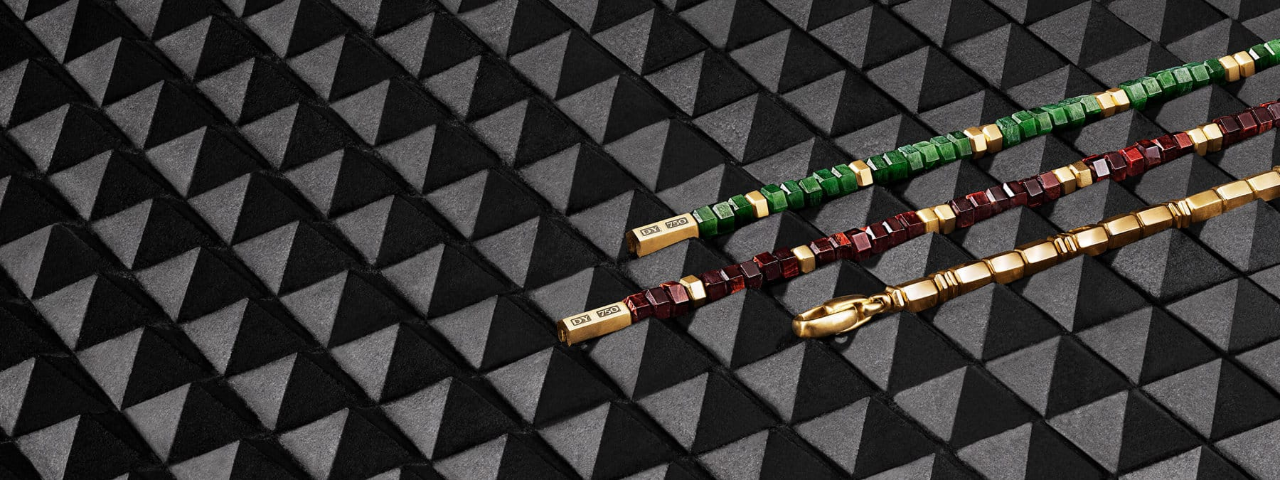 A color photograph shows a row of three David Yurman men's bracelets from the Hex collection against a black background. The bracelets are crafted from 18K yellow gold six-sided beads with or without jade six-sided beads or red tiger eye's six-sided beads