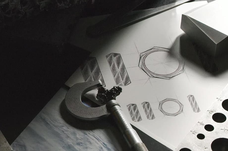 A close-up of jeweler's tools next to black-and-white sketches of band rings.