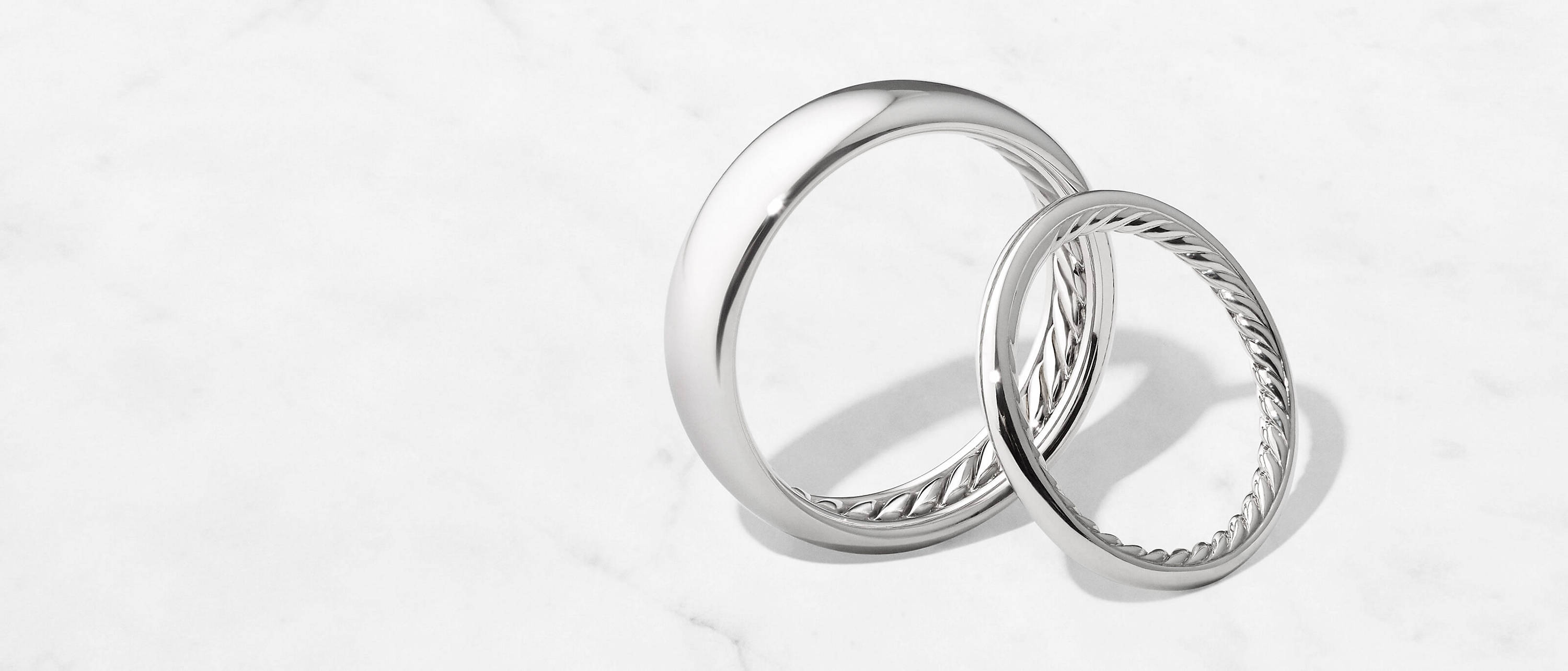 A DY Eden women's band in platinum leans against an upright DY Classic men's band in platinum on a marble surface.