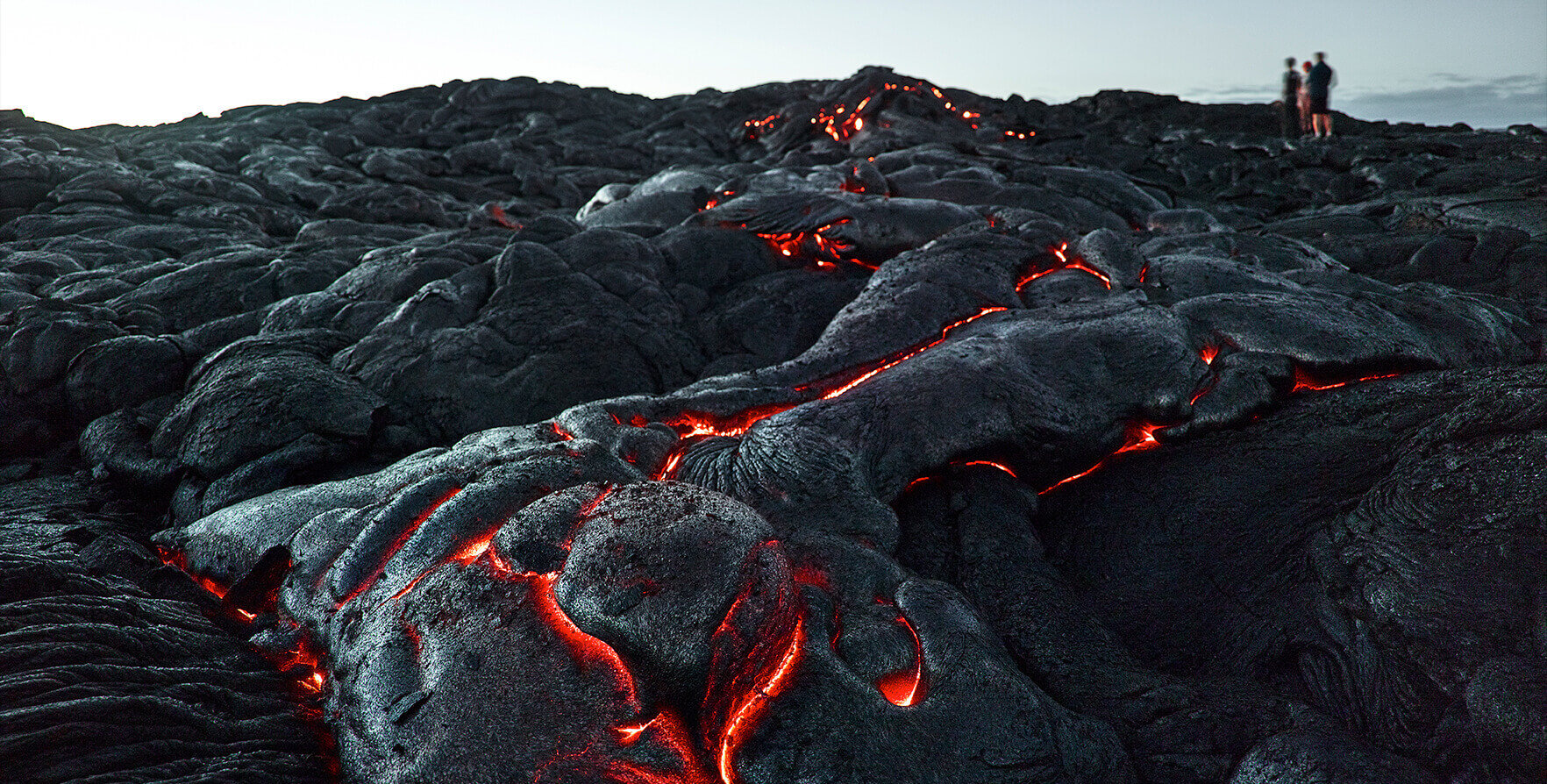 A color photo showing rivers of volcanic magma cooling into black rock with three figures of people standing on the horizon.