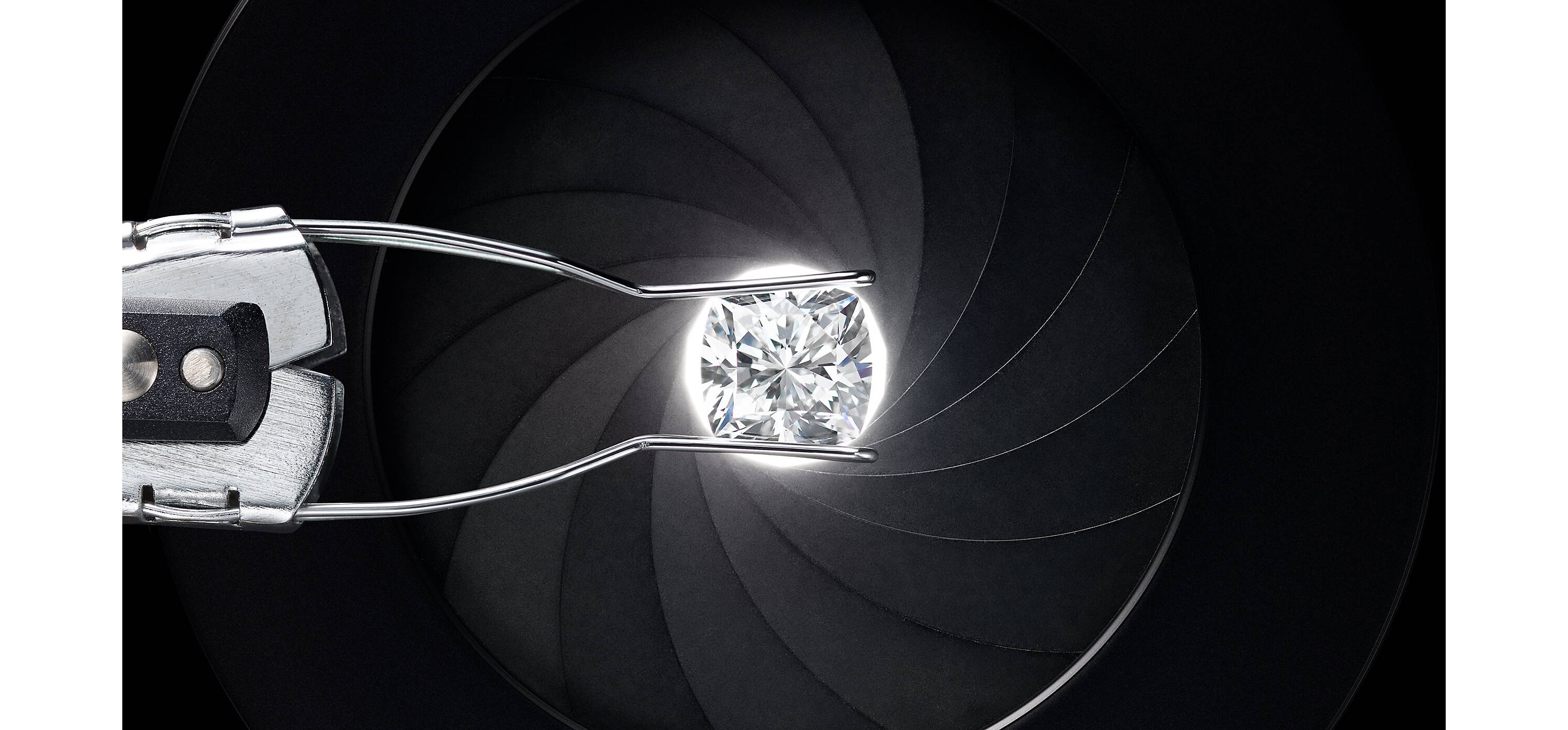 An overhead shot of a metal clamp holding a cushion-cut diamond above a white light shining from a black aperture.