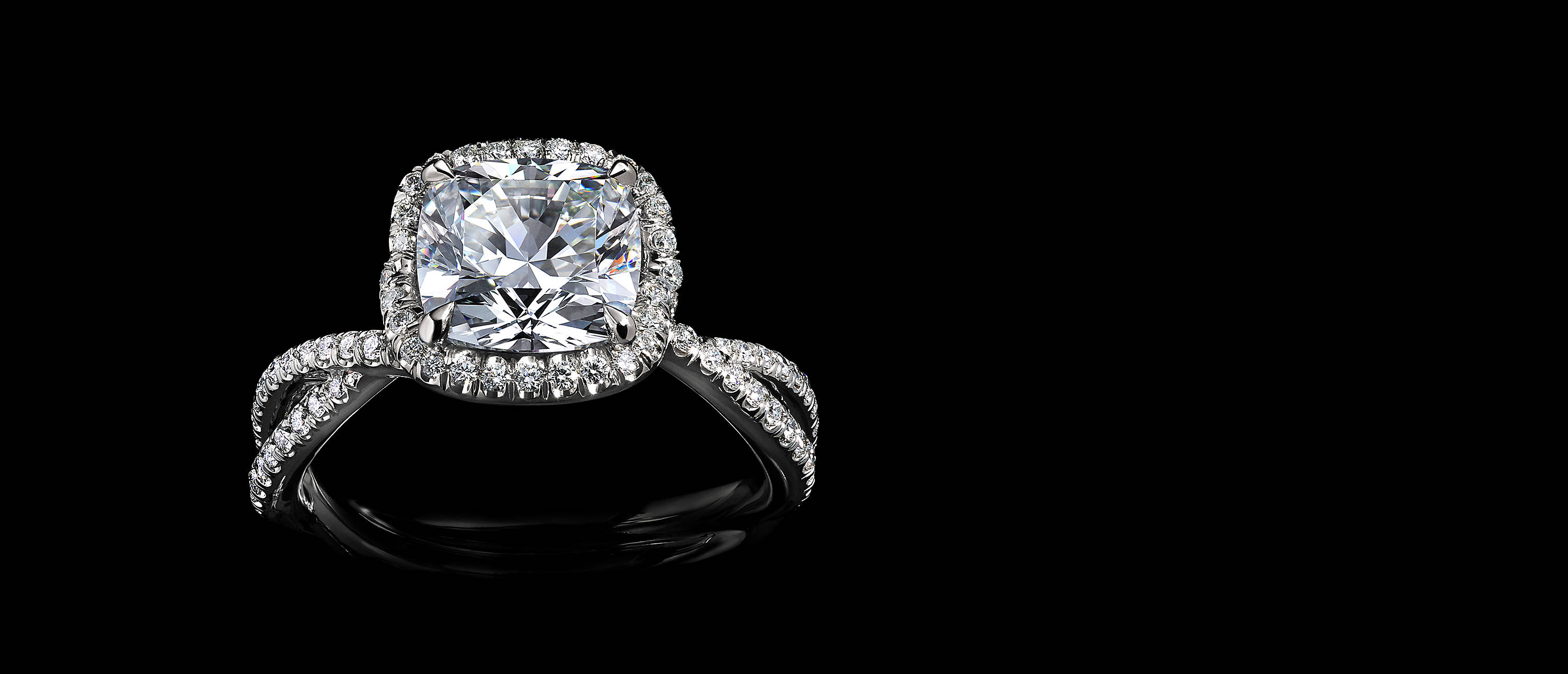 Shot against black, a DY Lanai engagement ring in platinum with a DY Signature Cut center stone, a halo of pavé diamonds and a twisted shank covered with pavé diamonds.