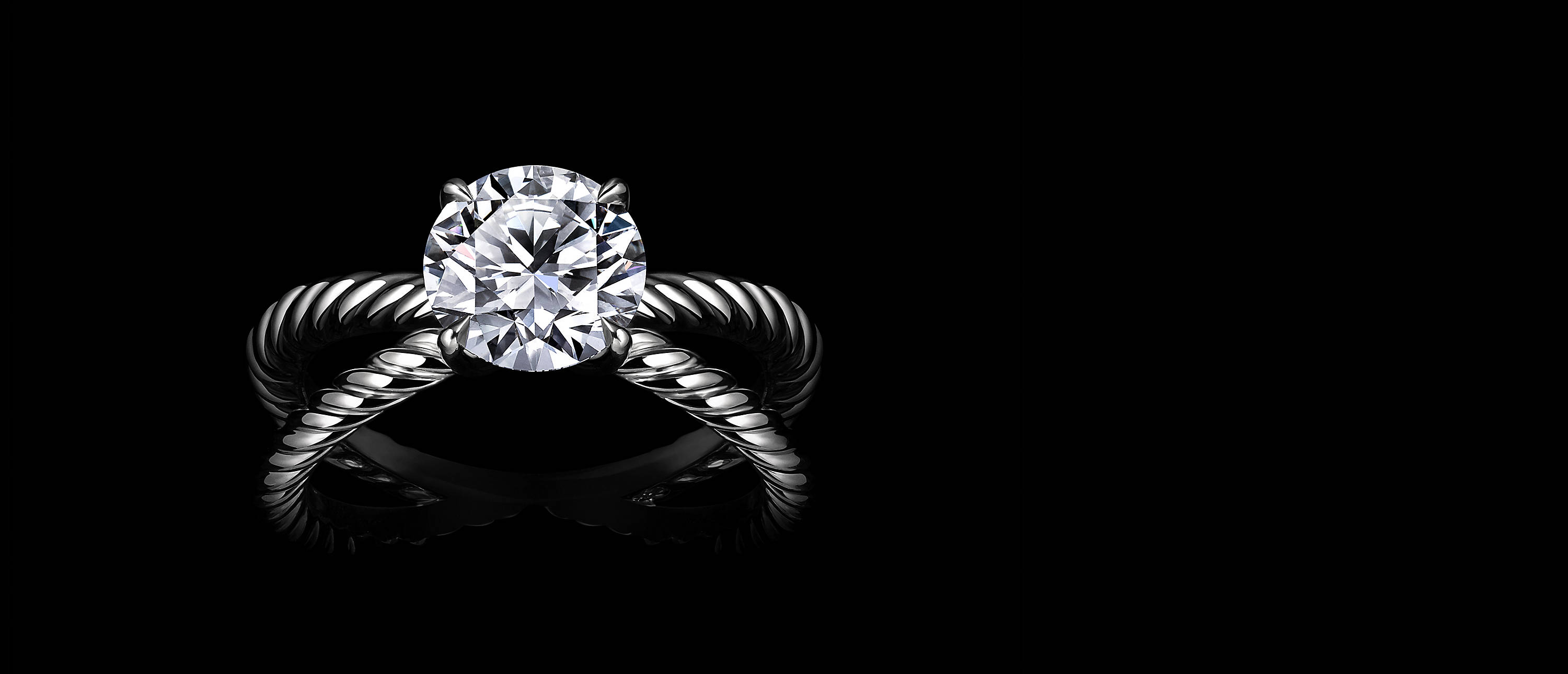Shot against black, a DY Crossover® engagement ring with a round brilliant center diamond at the center of two intersecting platinum Cable bands.