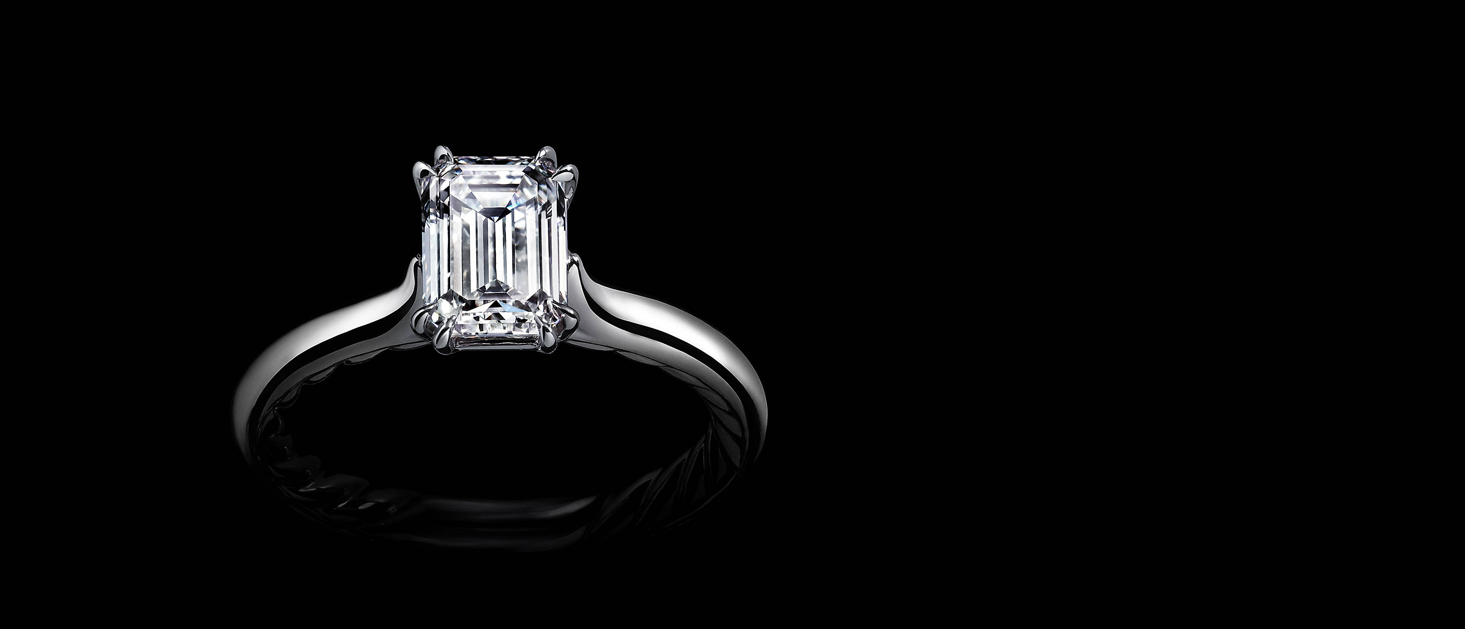 Shot against black, a David Yurman engagement ring in platinum with an emerald-shaped center diamond and Cable on the inside of the shank.