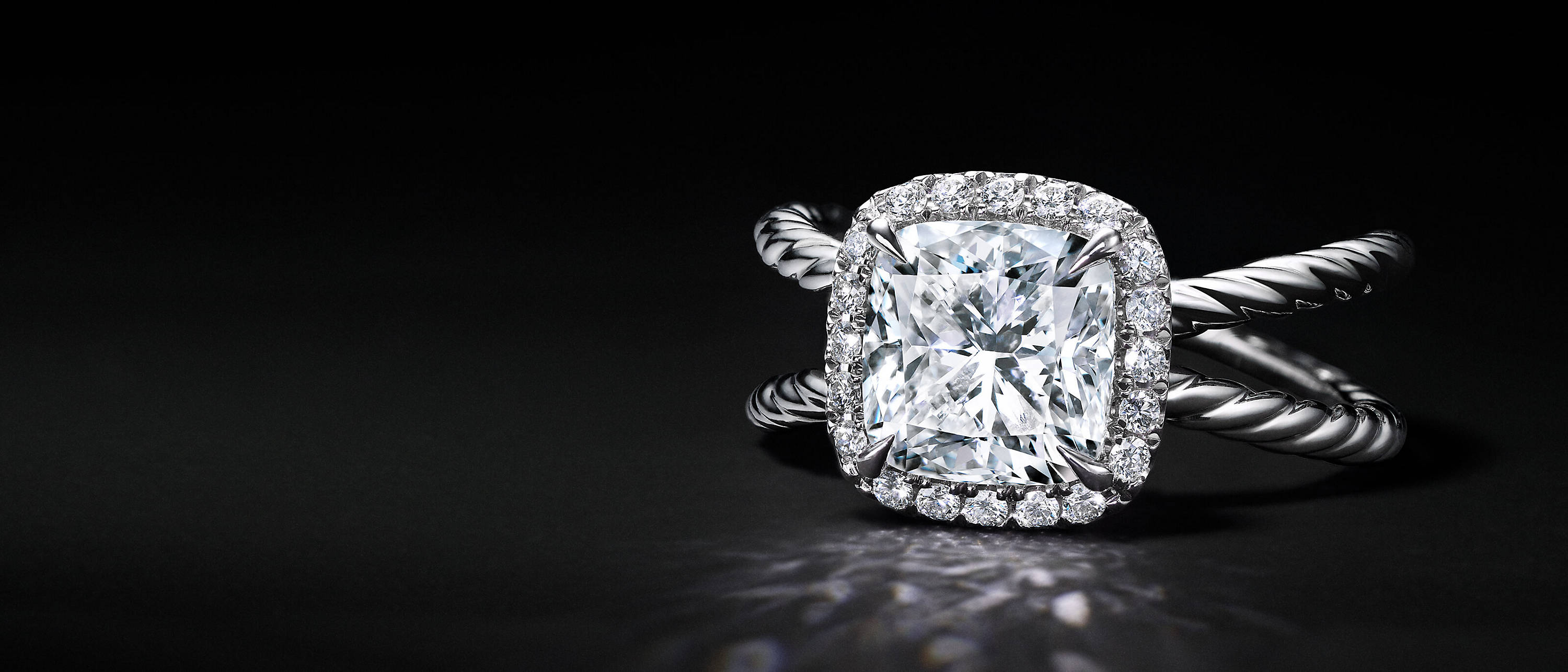A David Yurman Crossover engagement ring in platinum with a cushion-cut center stone and a halo of diamonds shot against a black backdrop. The ring is placed so that its diamonds are in full view, casting light on the surface.