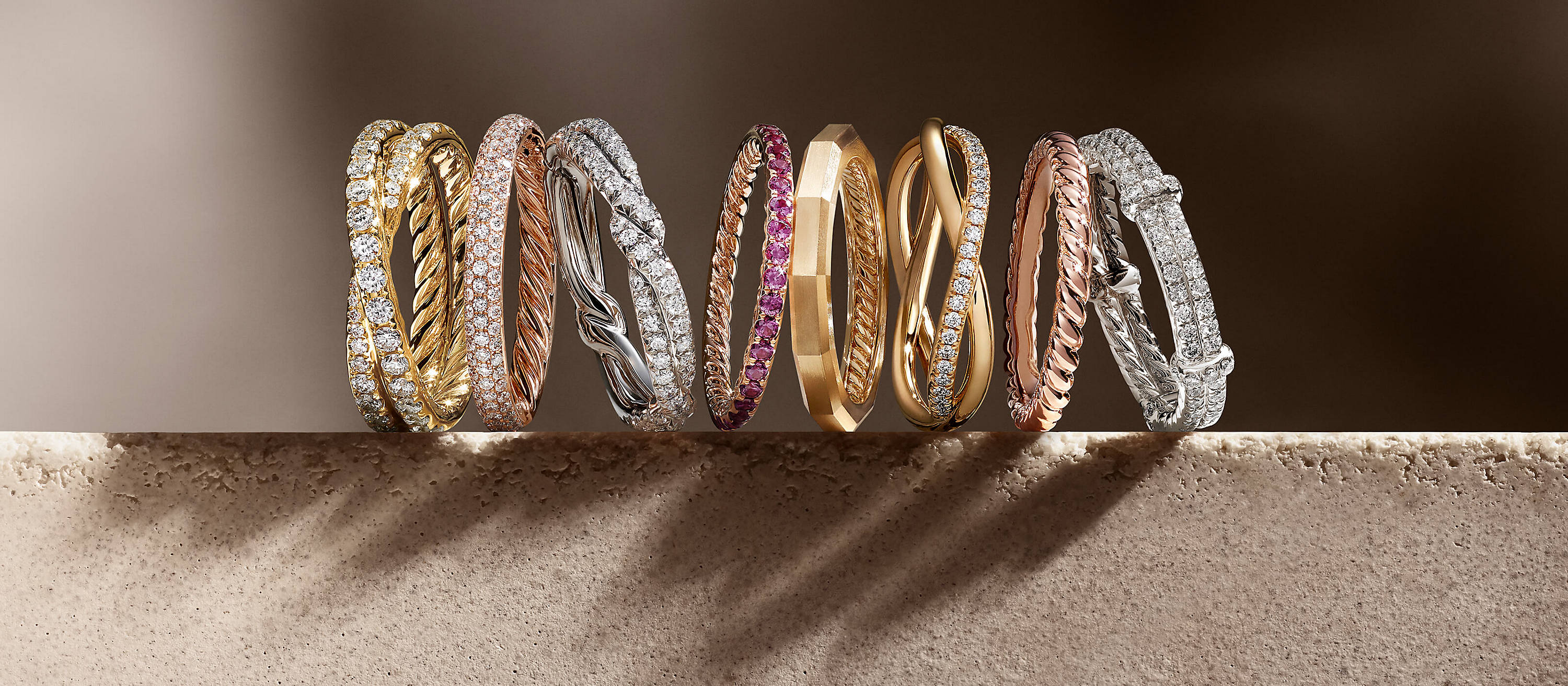 David Yurman DY Crossover, DY Eden, DY Wisteria, DY Delaunay, DY Lanai, DY Unity and DY Astor band rings, in 18K yellow or rose gold or platinum with or without diamonds or pink sapphires, in a horizontal stack on a sandstone block casting long shadows.