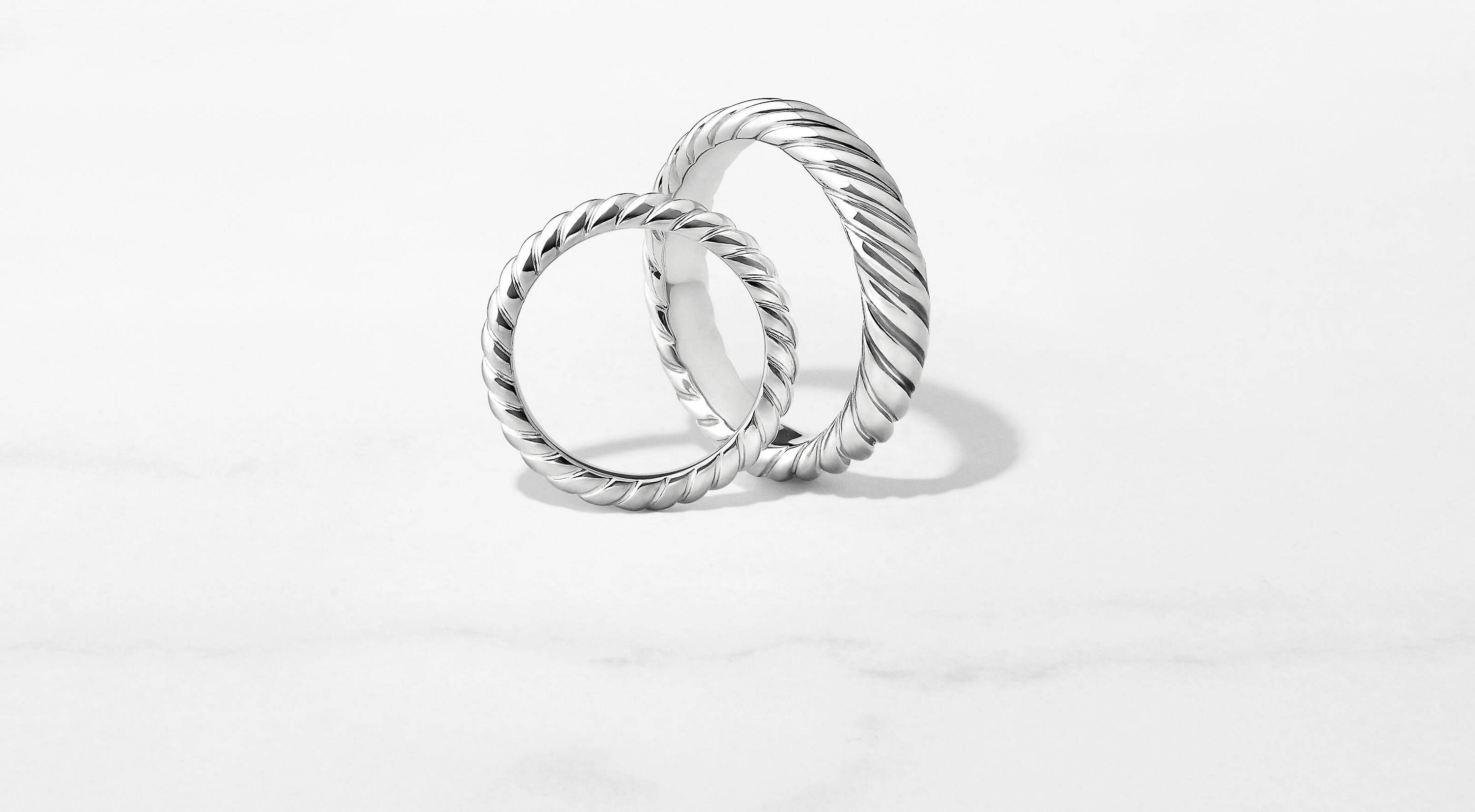 A DY Unity women's band in platinum leans against an upright Cable men's band in 18K white gold on a marble surface.