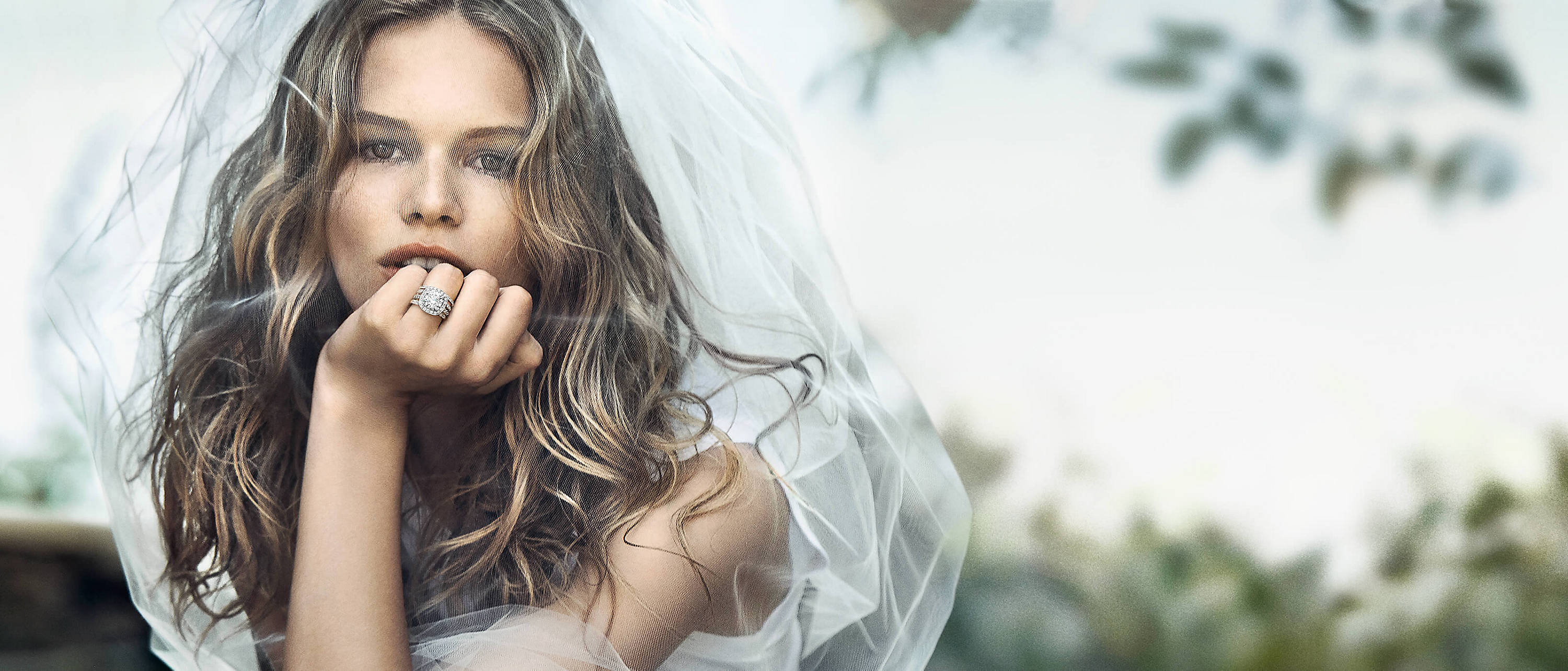 A color photo of model Anna Ewers sitting in a forest wearing a white veil, David Yurman diamond wedding bands and an engagement ring, a white tank top and ripped jeans.