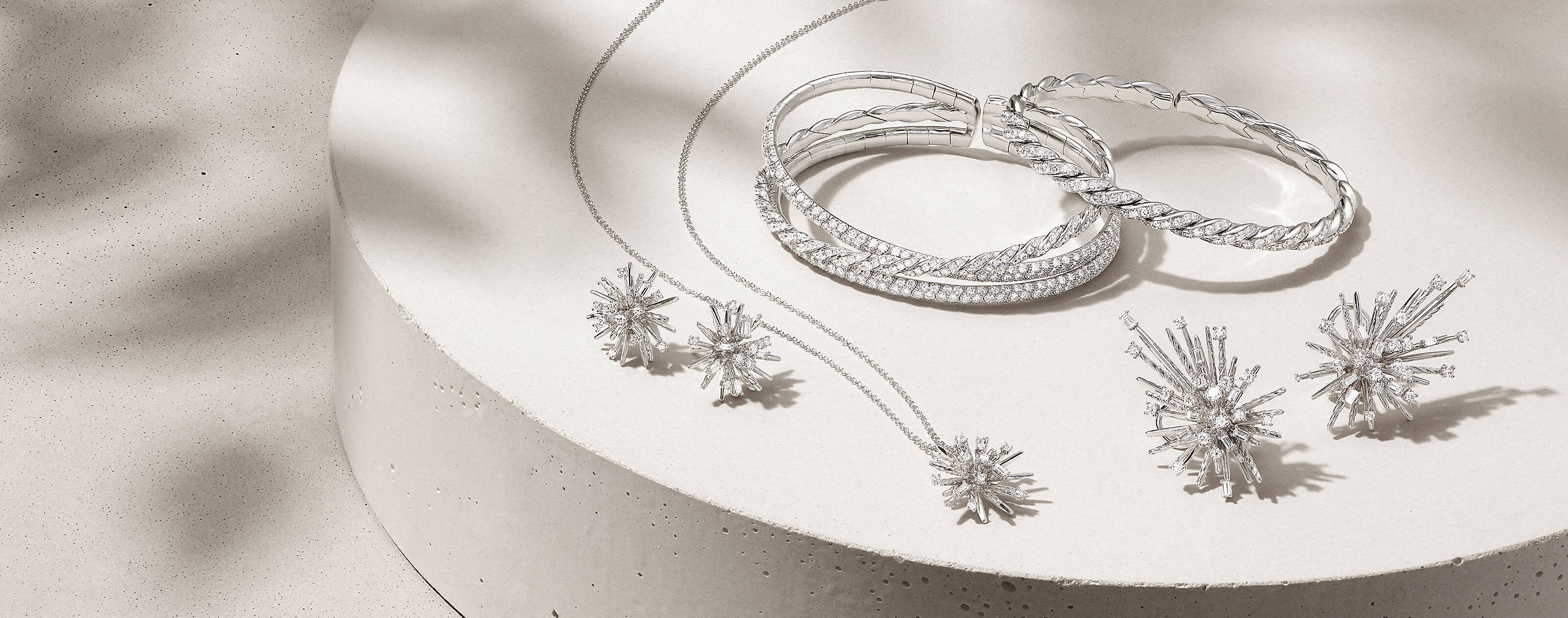 An overhead shot of stud and climber earrings, and a pendant necklace from the Supernova Collection placed below Stax and Pavéflex bracelets—all in 18K white gold with diamonds—on a round beige stone with leafy shadows.