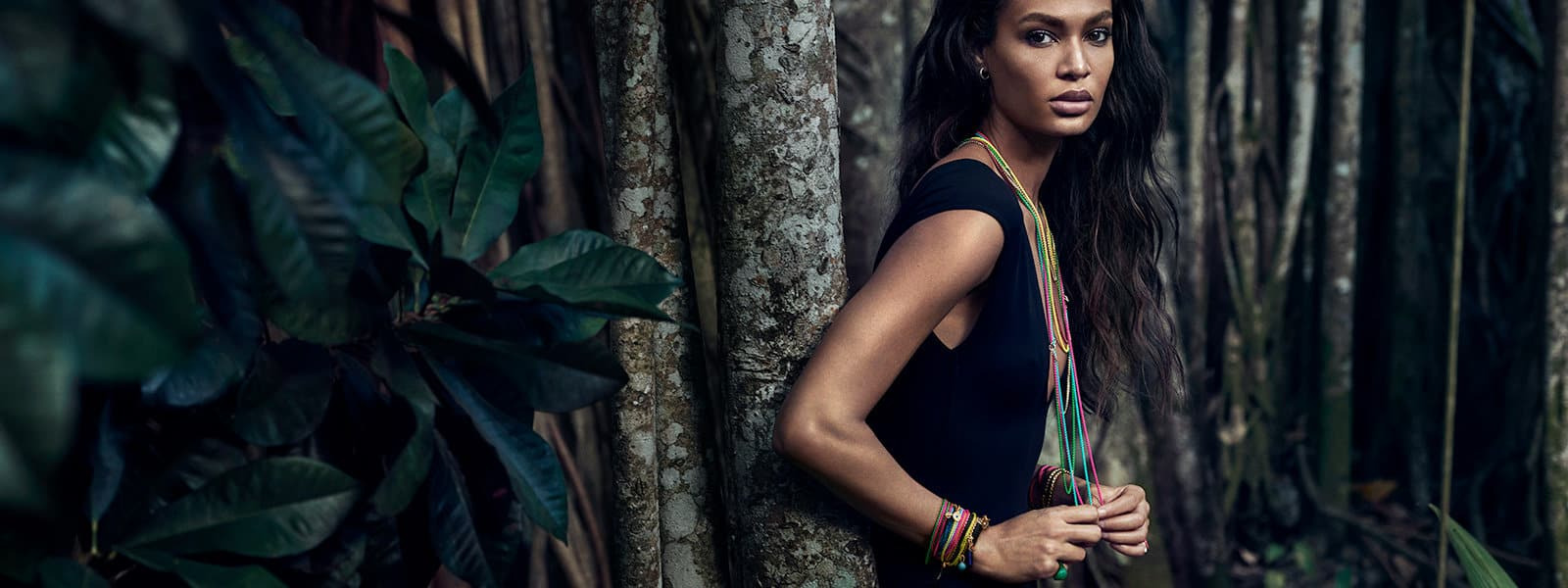 DY Bel Aire colourful chain necklaces in acrylic-coated stainless steel with 14K yellow gold and various amulets on model Joan Smalls in a forest.