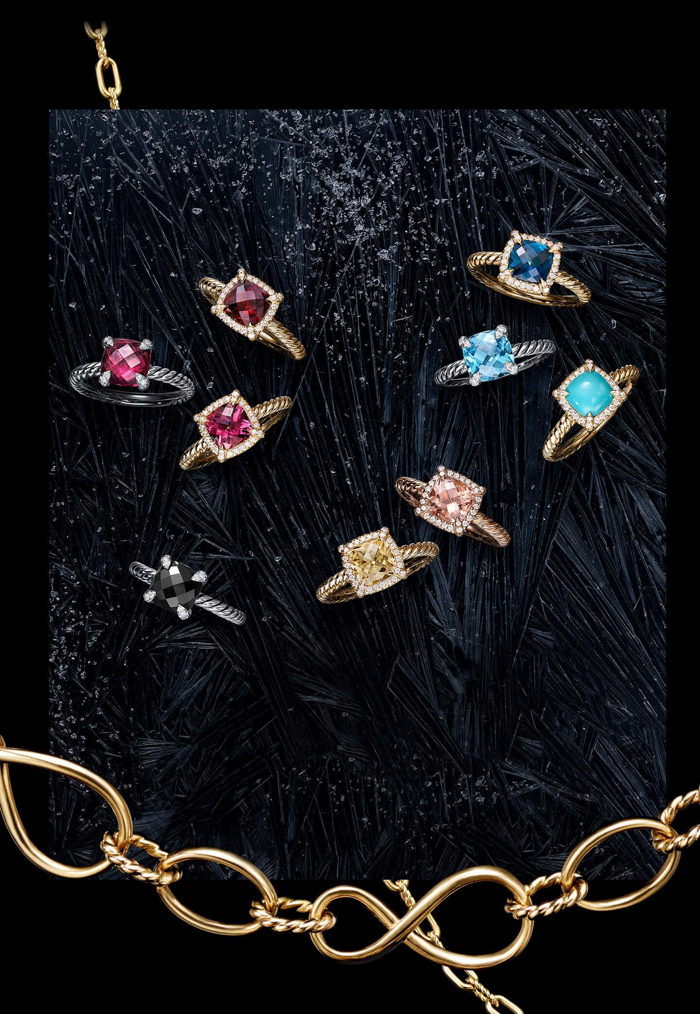 An overhead shot shows six David Yurman Châtelaine rings placed on top of a black frozen surface with large ice crystals. The women's jewelry is crafted from 18K yellow gold or sterling silver with garnet, blue topaz or chrysoprase center stones and pavé white diamond–encrusted prongs or bezels.