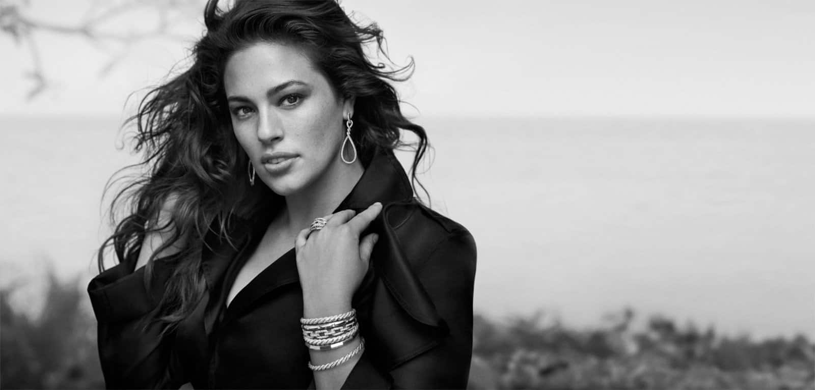 A black-and-white photo of model Ashley Graham wearing a black top, David Yurman Continuance® drop earrings, a Stax ring, and a stack of bracelets from the Stax and Pure Form® collections.