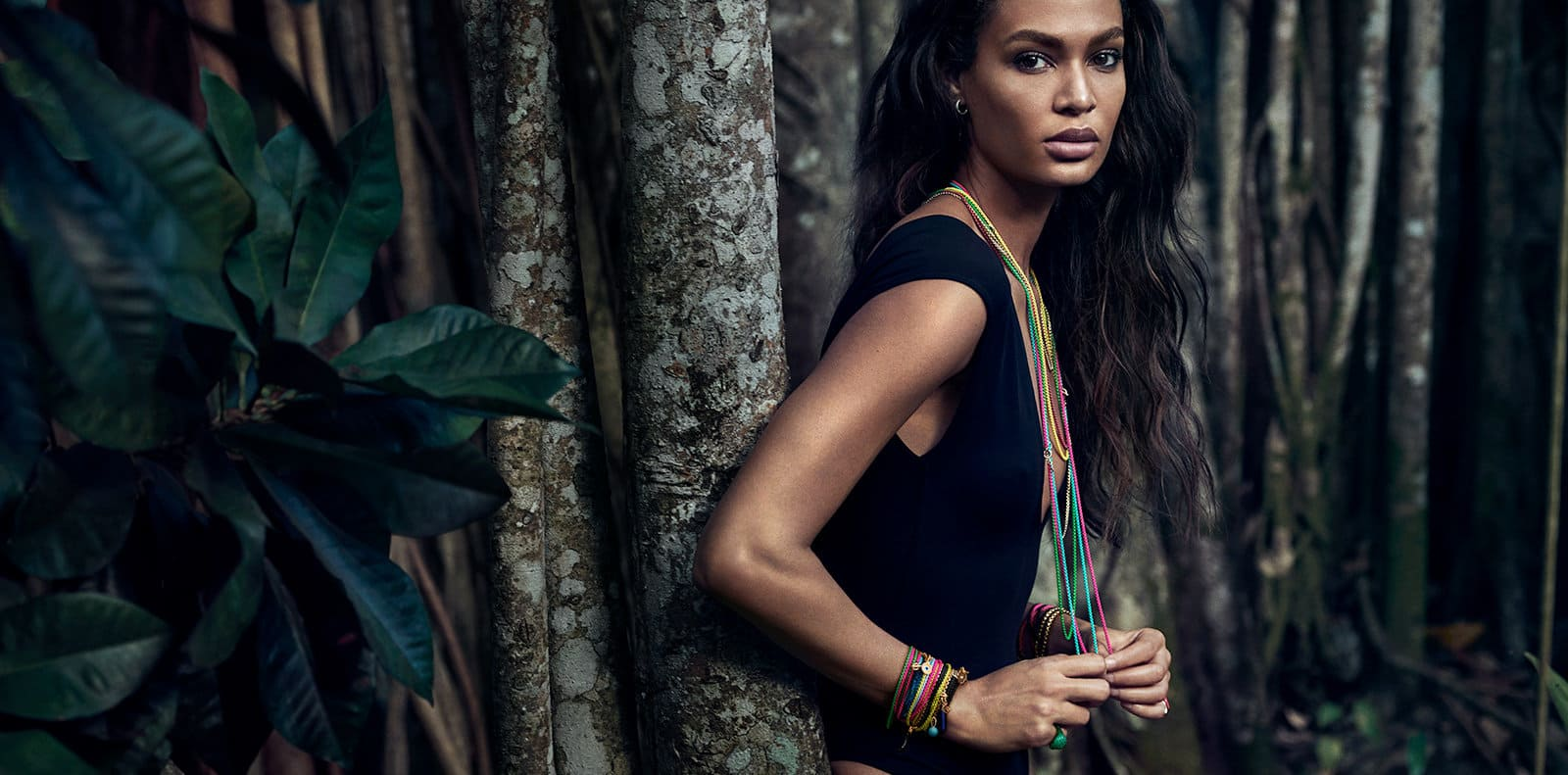 DY Bel Aire colorful chain necklaces in acrylic-coated stainless steel with 14K yellow gold and various amulets on model Joan Smalls in a forest.