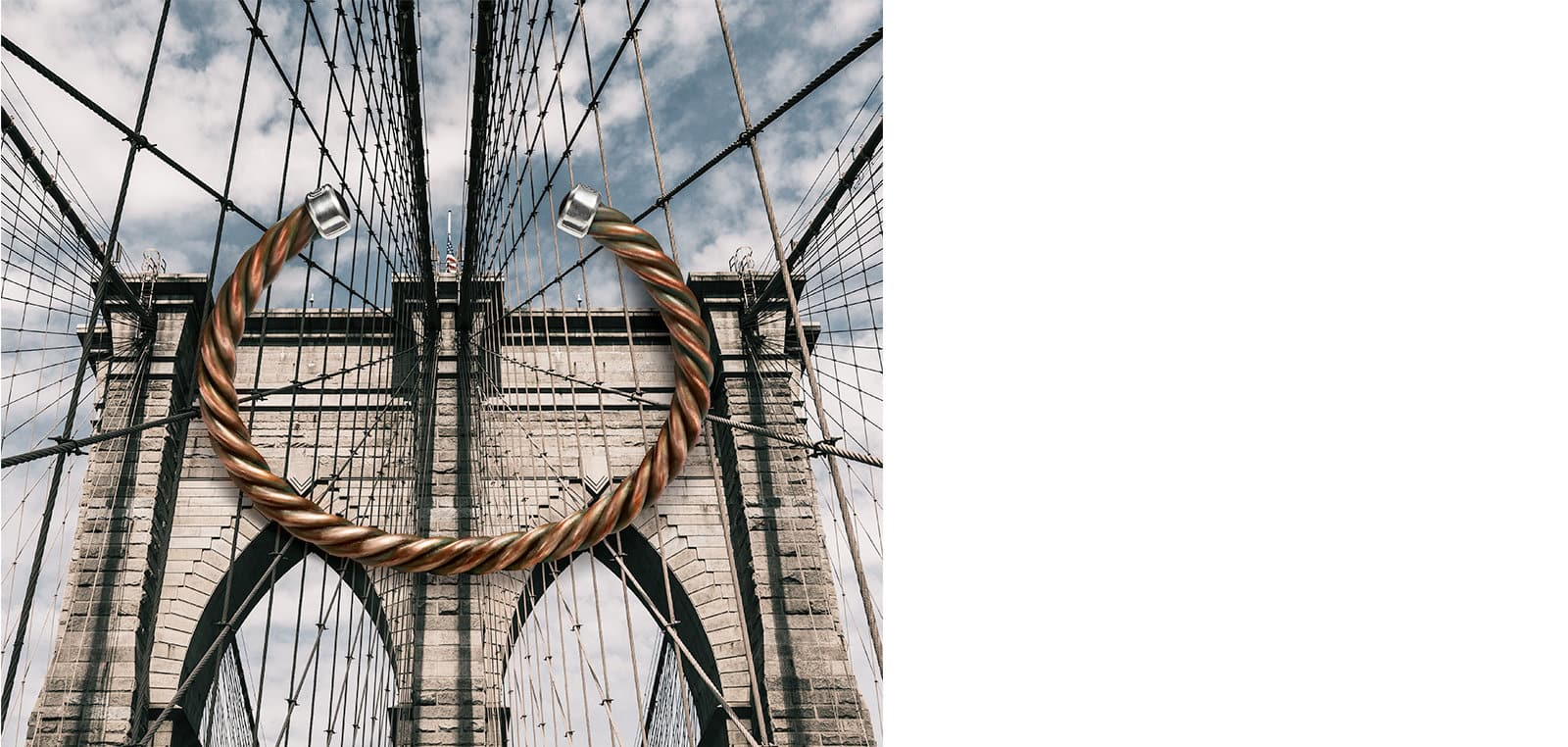 A David Yurman men's Cable bracelet in copper with black onyx end caps atop a photo of the Brooklyn Bridge.