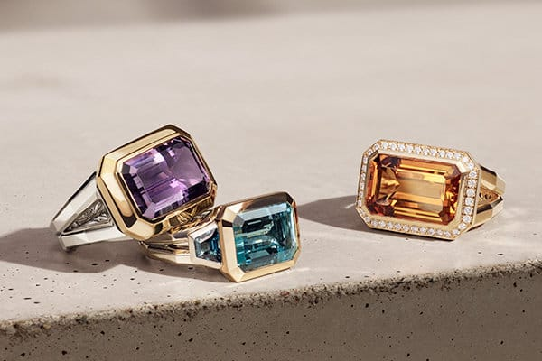 David Yurman Novella rings in sterling silver with 18K yellow gold and amethyst or blue and Hampton blue topaz, or 18K yellow gold with Madeira citrine and diamonds, on a beige-colored stone with long shadows.