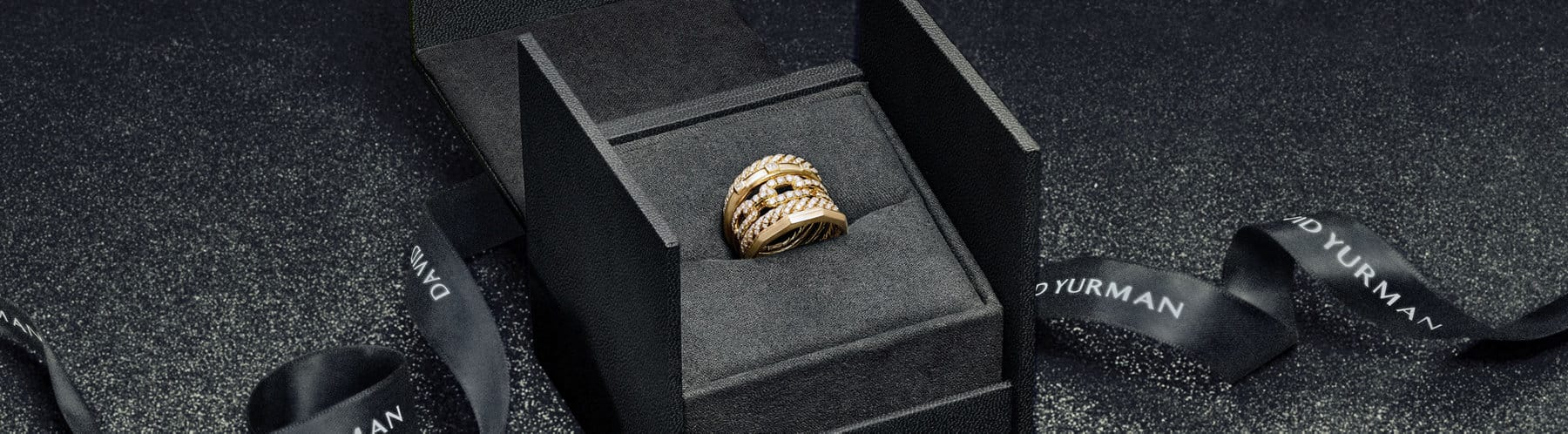 A color photo shows a David Yurman gift box with a gold and diamon Stax five row ring.