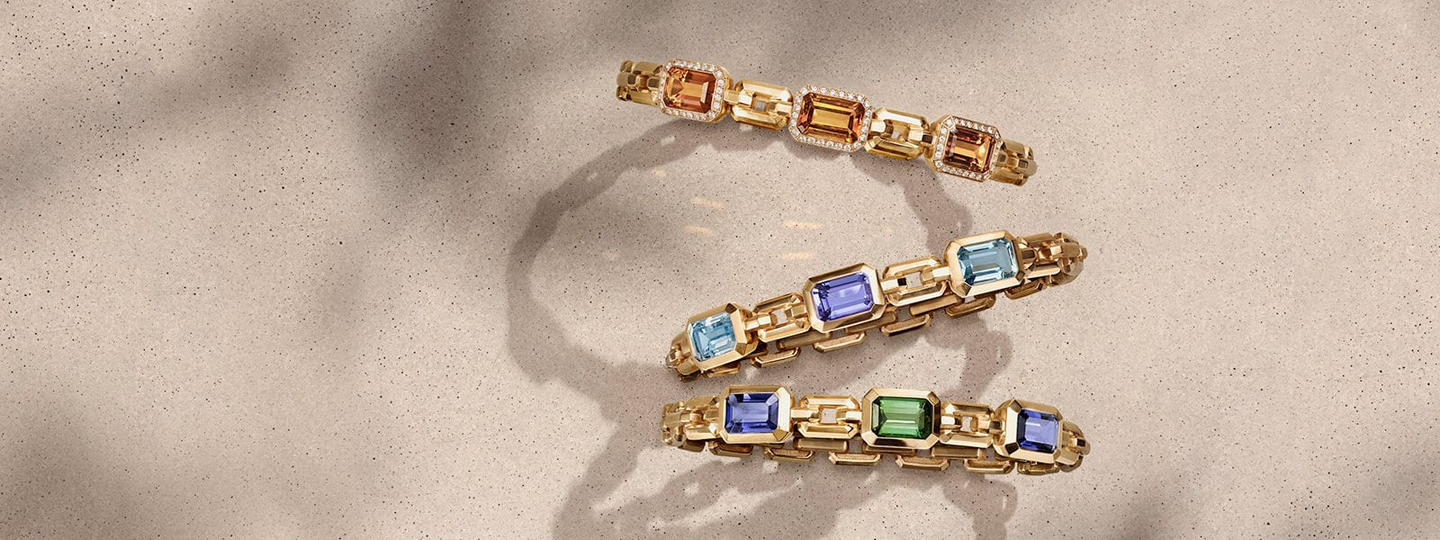 David Yurman Novella bracelets in 18K yellow gold with Madeira citrine and white diamonds, blue topaz and tanzanite, or iolite and green tourmaline, in a vertical stack casting long shadows on a sandy-colored stone.