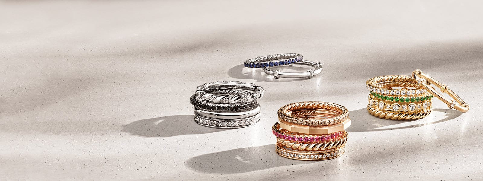 Four stacks of David Yurman band rings in 18K white, yellow or rose gold with colored gemstones casting long shadows on a beige stone surface.
