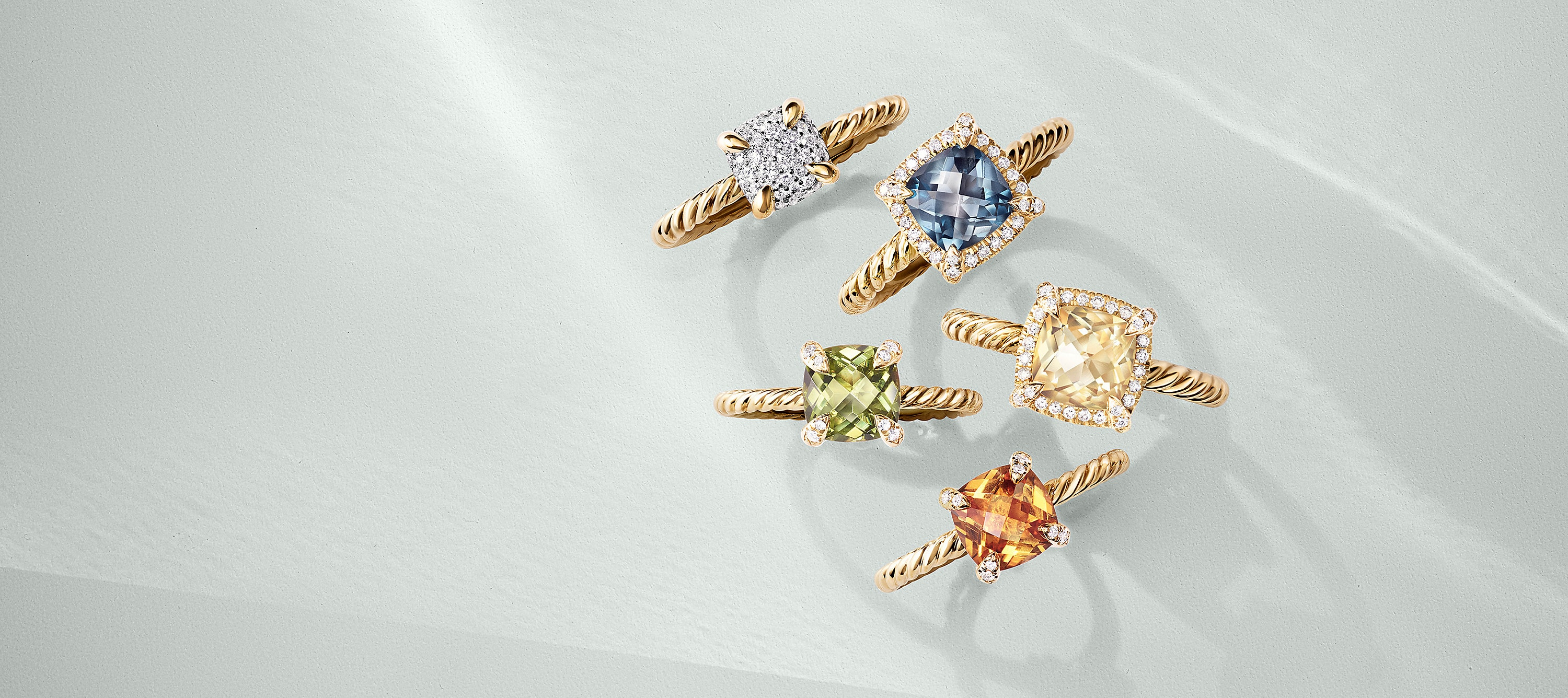 A color photo shows five David Yurman women's Châtelaine rings placed on a white background with soft shadows. The jewelry is crafted from 18K yellow gold with cushion-shaped center stones including pavé diamonds, Hampton blue topaz, peridot, or Champagne citrine or citrine.