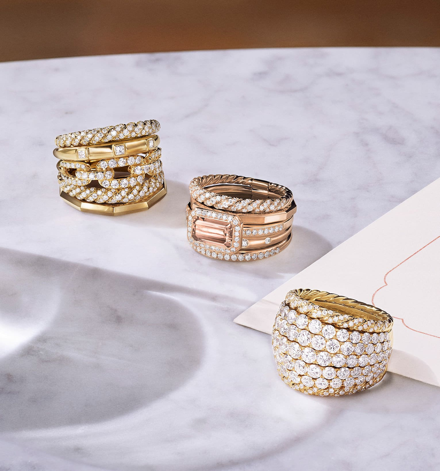 A color photograph shows three David Yurman women's multi-row rings from the Stax and High Jewelry collections scattered on a grey marble surface with soft shadows, a white notecard and a carafe of water. The jewelry is crafted from 18K yellow gold with pavé white diamonds. One ring features an emerald-cut morganite center stone.