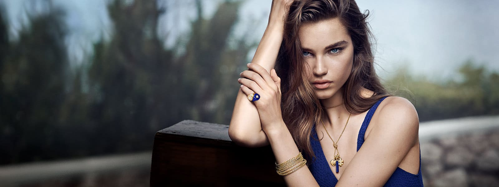 Model Meghan Roche in a tropical forest wearing a blue tank top with David Yurman Pinky Rings in 18K yellow gold or navy enamel-covered 18K yellow gold with white diamonds, chains in 18K yellow gold and Amulets in 18K yellow gold with white diamonds or lapis lazuli.