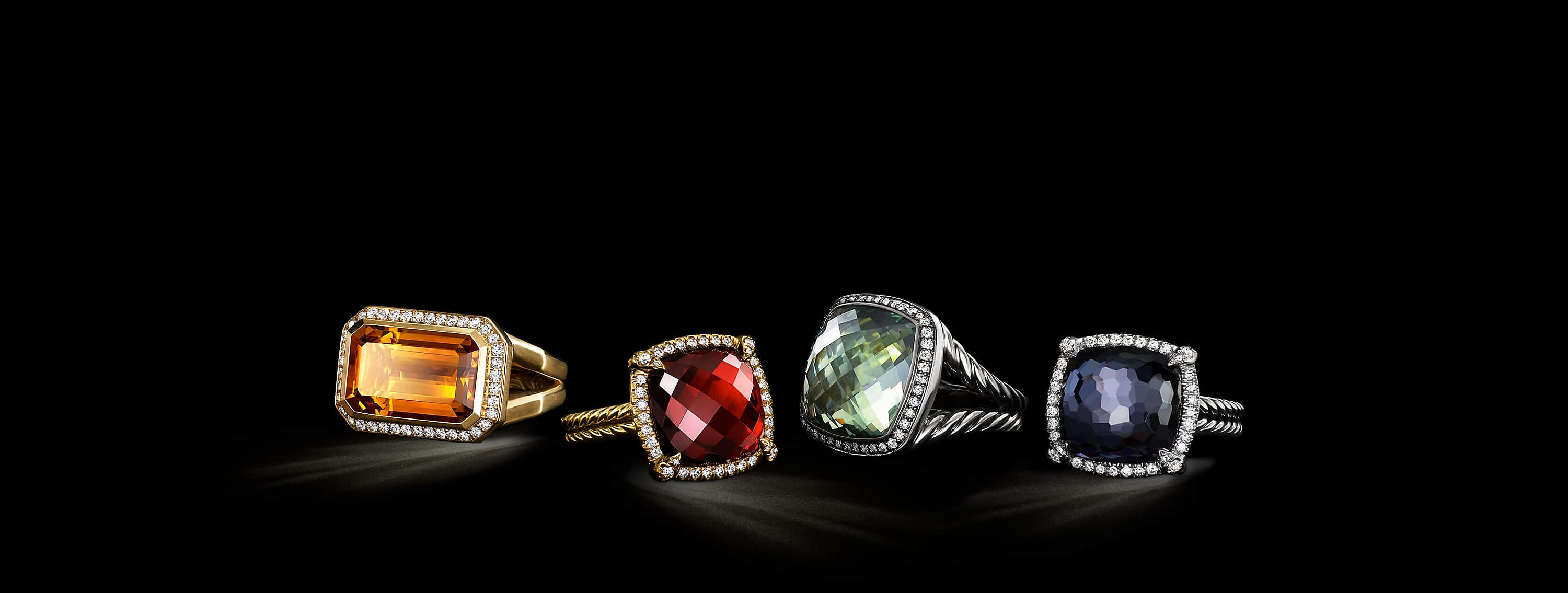 A  color photograph shows four David Yurman women's rings from the Châtelaine, Albion and Novella collections floating in front of a starry night sky. The jewelry is crafted from 18K yellow or rose gold or sterling silver with pavé diamonds, citrine, garnet, prasiolite and black orchid.