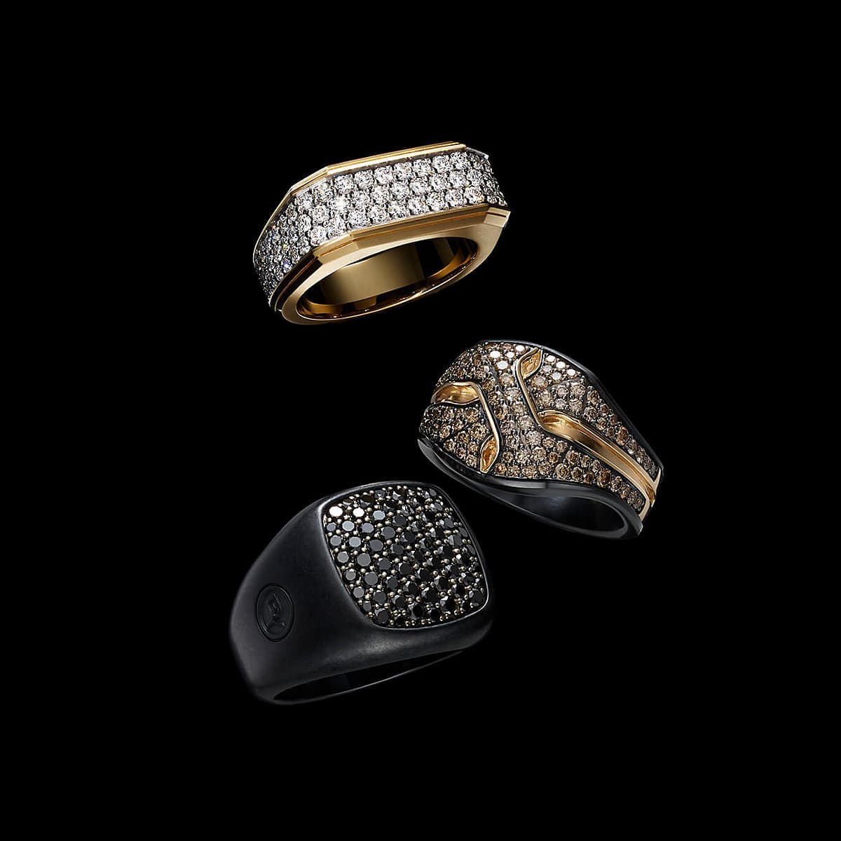 A color photo shows three David Yurman men's rings from the Pavé and Armory collections floating in front of a starry night sky. The top ring  is crafted from 18K yellow gold with white diamonds, and the middle ring is crafted from black titanium with 18K rose gold and cognac diamonds. The final ring is crafted from black titanium with black diamonds.