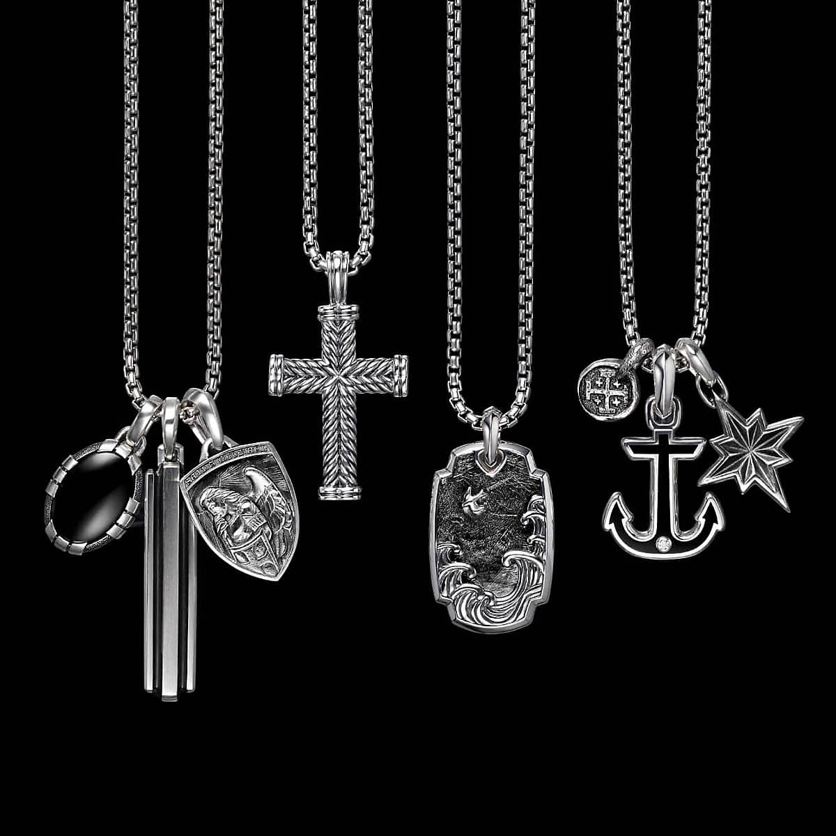 A color photograph shows four David Yurman men's box-chain necklaces in sterling silver hanging in front of a black background with white latitude and longitude lines. Each necklace is strung with one or three David Yurman men's amulets crafted from sterling silver. From left is a Southwest amulet with black onyx, a Deco amulet, a Saint Michael shield-shaped amulet, a Chevron cross, a Waves tag with forged carbon, a Shipwreck coin amulet, a Maritime anchor with black onyx and a single diamond and a Maritime North Star amulet.