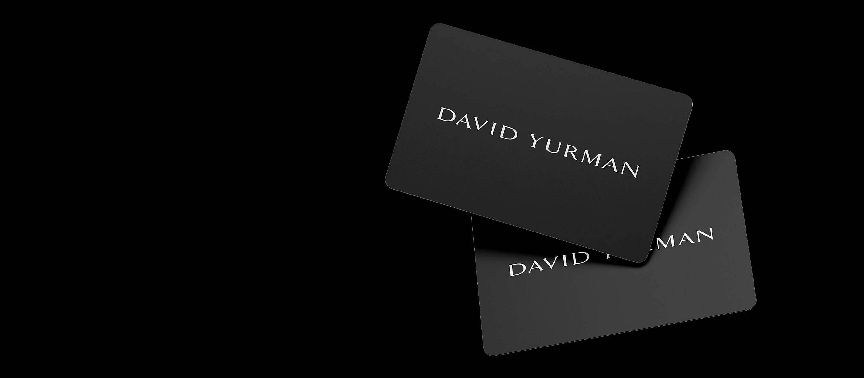 A color photo shows two David Yurman black gift cards floating in a starry night sky with white clouds.