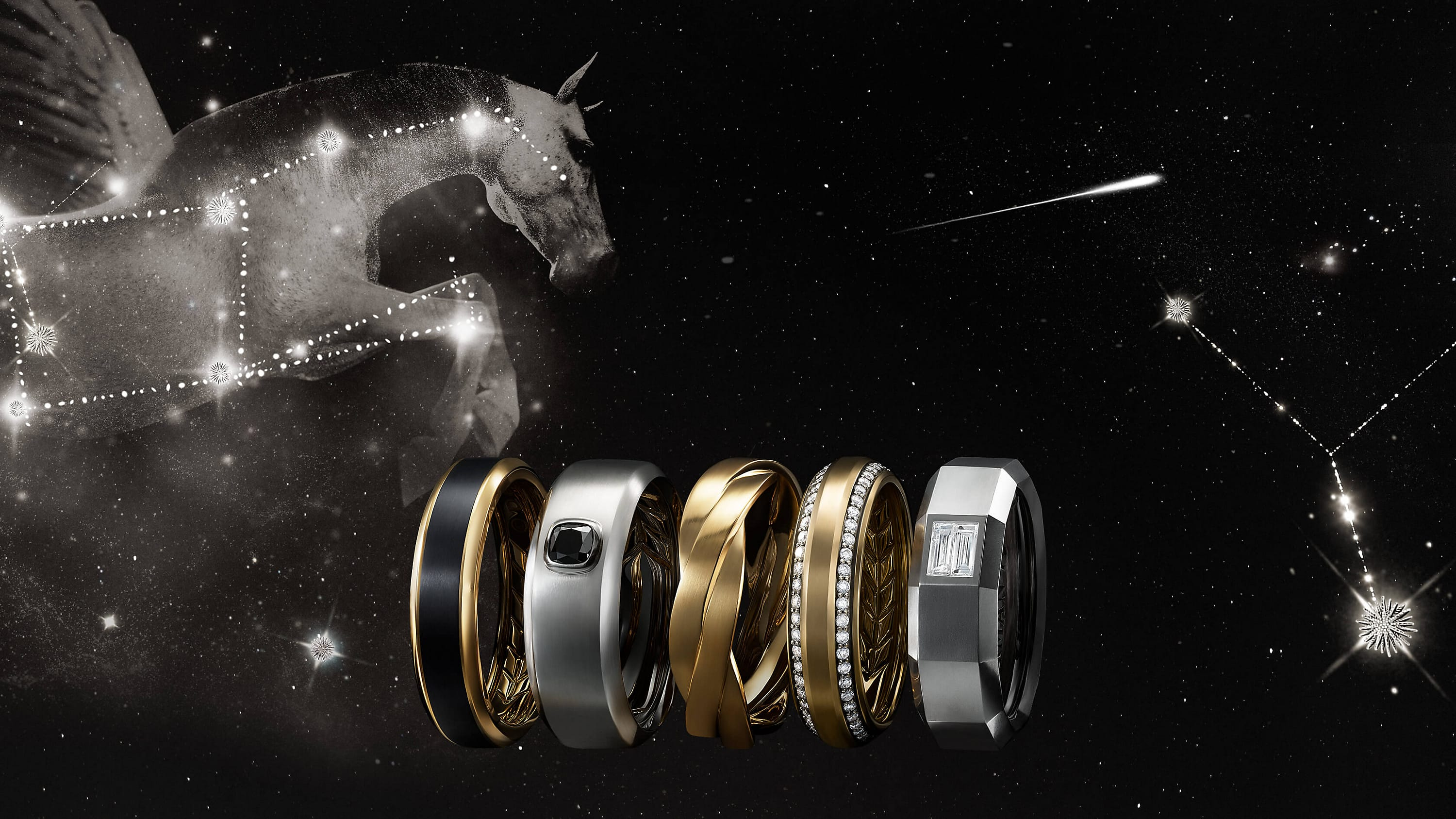 A color photo shows a horizontal stack of five David Yurman men's bands floating in front of a starry night sky with a Pegasus flying behind a constellation of Starburst-shaped stars. Three of the men's rings are crafted from 18K yellow gold with or without pavé white diamonds or black titanium. Two of the rings are crafted from 18K white gold with or without black or white diamonds.