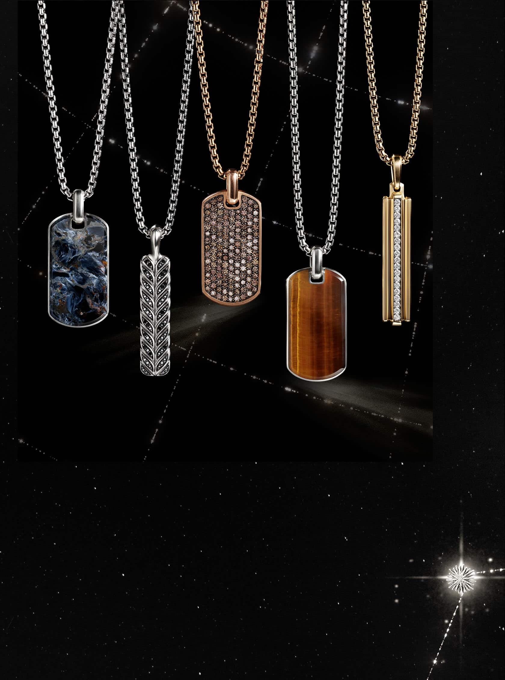 A color photograph shows five David Yurman men's tags strung on box chains hanging in front of a black-and-white background with latitude and longitude lines. Three of the tags are crafted from sterling silver with pietersite, black diamonds or tiger's eye. One tag is crafted from 18K rose gold with cognac diamonds. The final tag is crafted from 18K yellow gold with white diamonds.