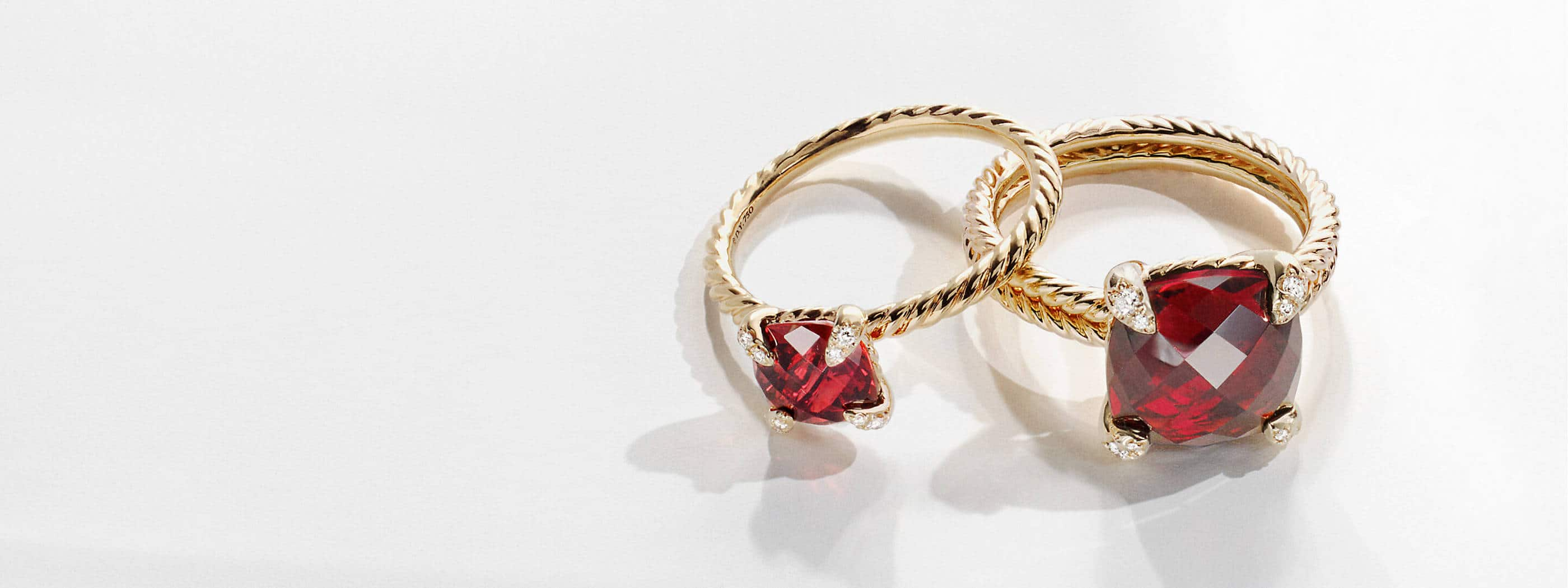 A color photograph shows a pair of David Yurman women's rings sitting on a white stone with shadows. The jewelry is crafted from Cabled 18K yellow gold with faceted garnet center stones. The rings have pavé diamonds on the prongs.