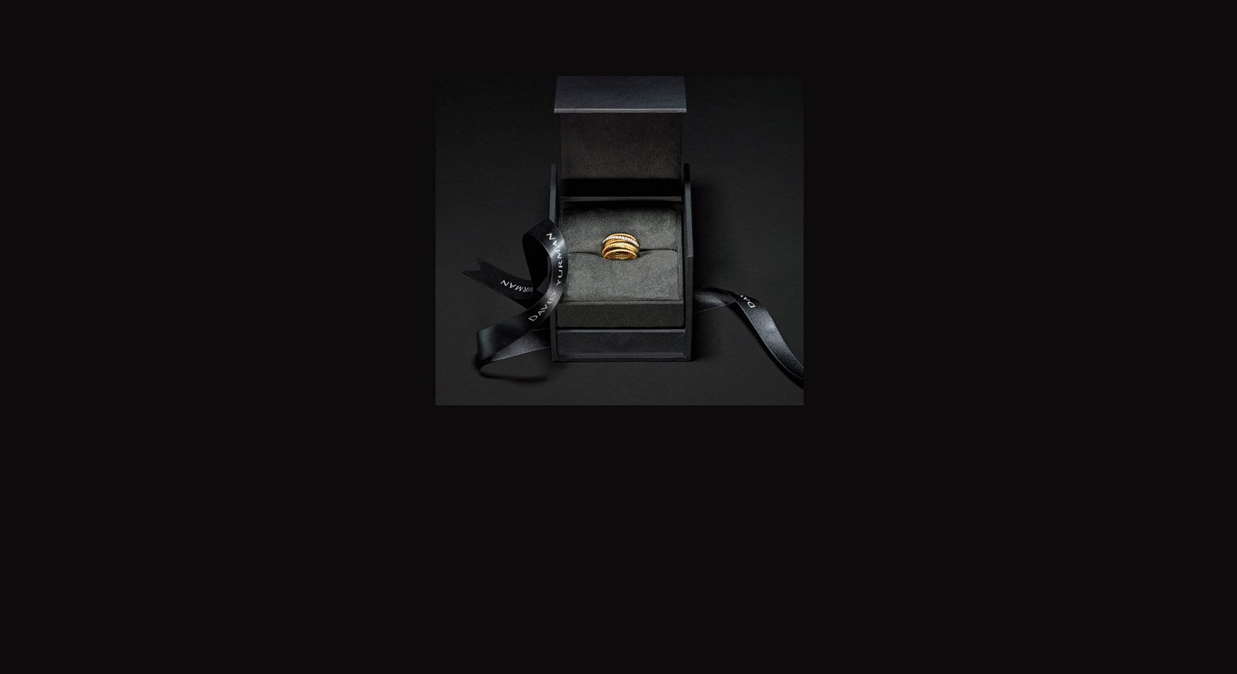 A color photo shows an open David Yurman black ring box on a black background. Inside is a David Yurman women's Crossover ring in 18K yellow gold with pavé diamonds. Underneath the box is a black ribbon featuring the David Yurman logo printed in white.