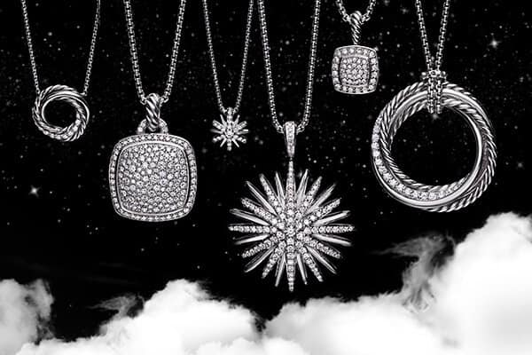 A color photo shows five David Yurman women's pendant necklaces hanging in a row in front of a starry night sky with white clouds. Two of the pendants are star shaped, two are cushion shaped and one is a circle of intertwined strands of Cabled and smooth metal. The women's jewelry is crafted from sterling silver or 18K white gold with pavé diamonds.