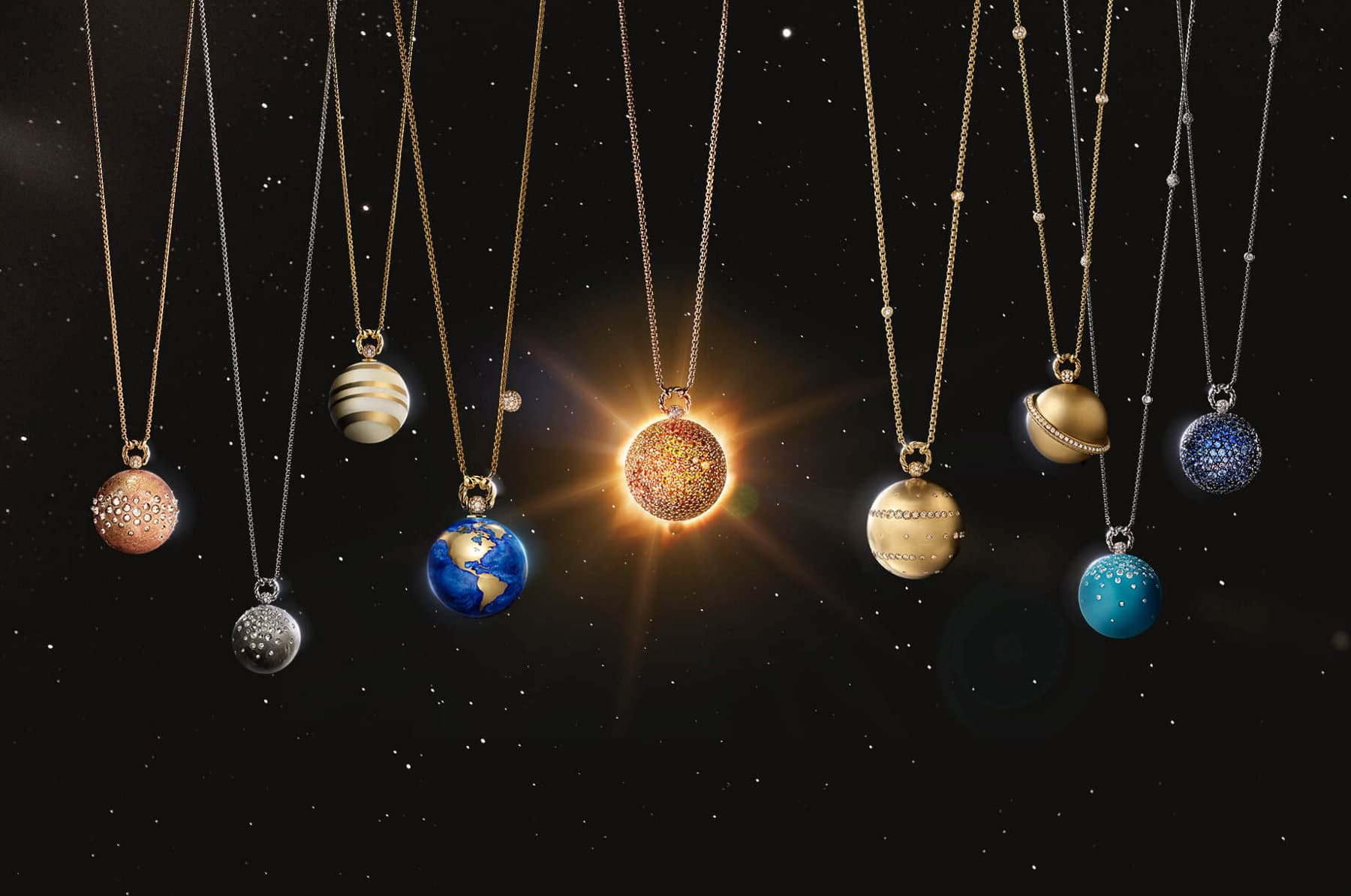 A color photo shows nine David Yurman Solari Planet necklaces in a row of in front of a starry night sky. Each necklace's pendant depicts a planet in the solar system with different gemstones and materials. In the center of the row is a pendant necklace depicting the sun with golden light shining behind it.