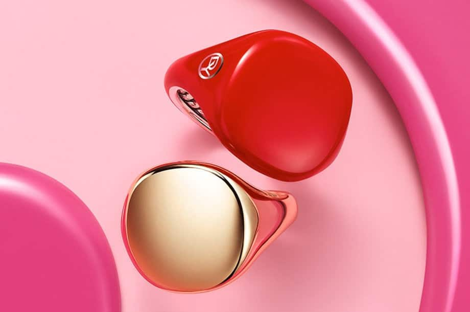 David Yurman Pinky Rings in 18K yellow gold or red ceramic-covered sterling silver against a bright pink backdrop.