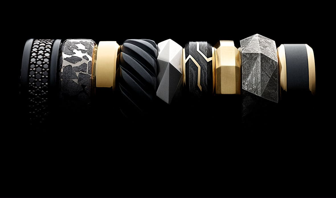 Men's Streamline, Meteorite, Beveled, Cable, Faceted and Forged Carbon bands in black titanium with or without black diamonds or 18K yellow gold; sterling silver with meteorite; 18K yellow gold with or without forged carbon; and platinum, in a row against a black background.