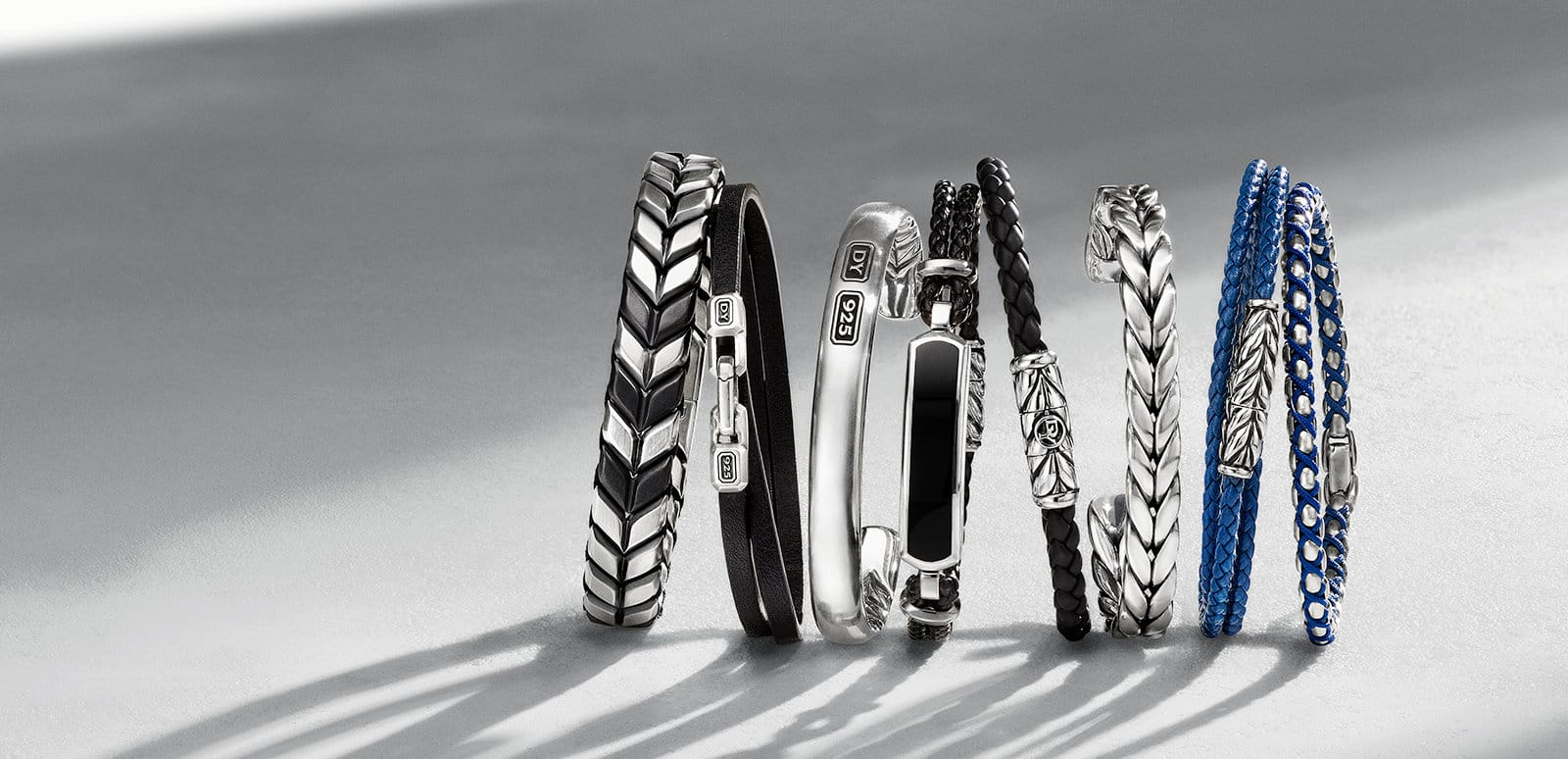 Chevron, Streamline, Exotic Stone, Chevron and Chain bracelets in sterling silver with or without black titanium; black leather with sterling silver; woven black leather with sterling silver and black onyx; woven black rubber with sterling silver; woven blue leather with sterling silver; and sterling silver and blue nylon, in a row on a textured white surface.