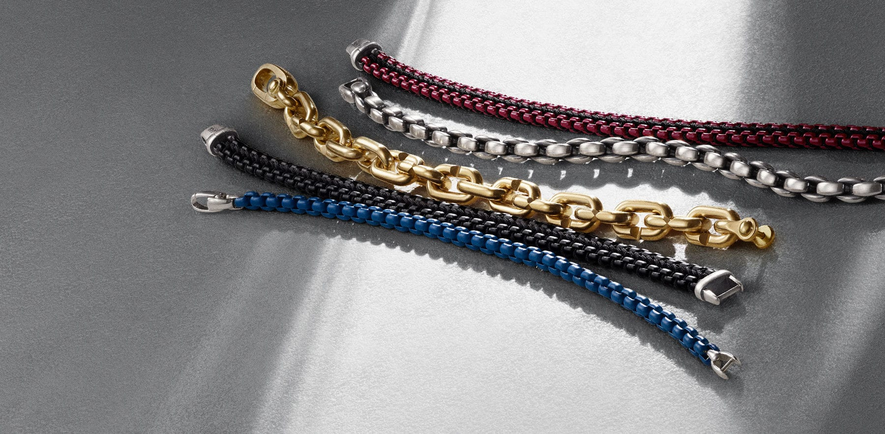 Men's DY Bel Aire and Chain bracelets in blue stainless steel, black stainless steel and black nylon, 18K yellow gold, sterling silver and a burgundy stainless steel with black nylon, arranged in a diagonal row atop a white textured surface.